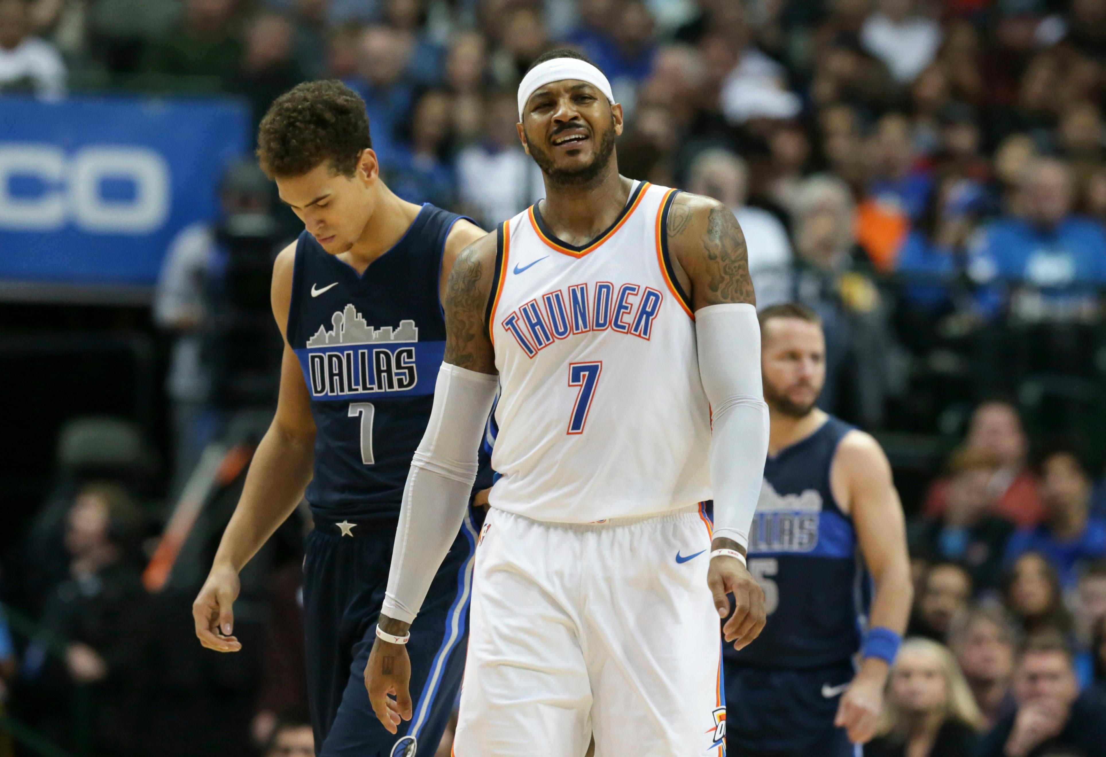 Oklahoma City Thunder forward Carmelo Anthony, foreground, reacts to a call in front of Dallas Mavericks forward Dwight Powell, left, during the second half of an NBA basketball game in Dallas, Saturday, Nov. 25, 2017. (AP Photo/LM Otero)