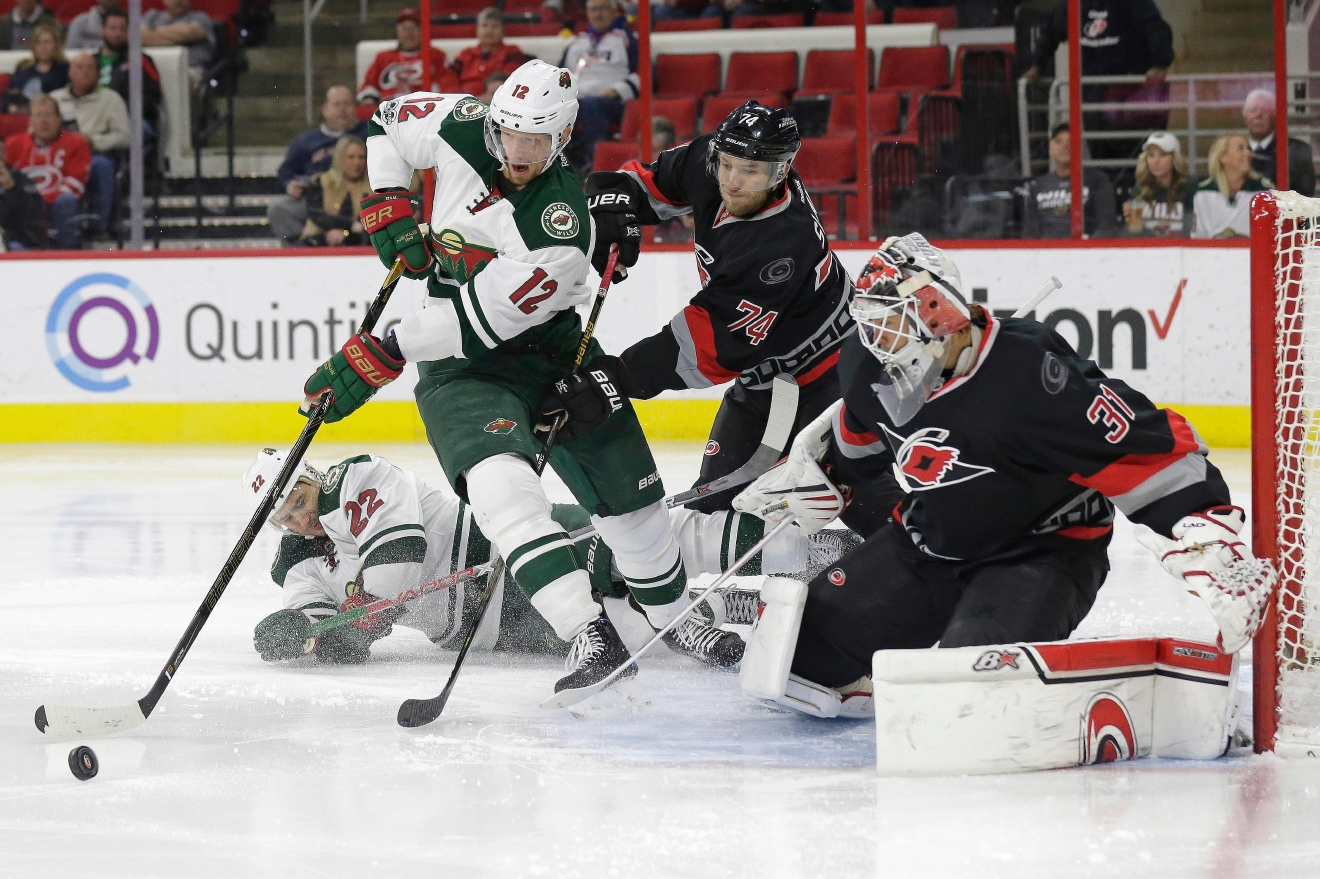 Minnesota Wild's Eric Staal (12) and Nino Niederreiter (22), of Switzerland, try to score while Carolina Hurricanes' Jaccob Slavin (74) and goalie Eddie Lack (31), of Sweden, defend during the first period of an NHL hockey game in Raleigh, N.C., Thursday, March 16, 2017. (AP Photo/Gerry Broome)