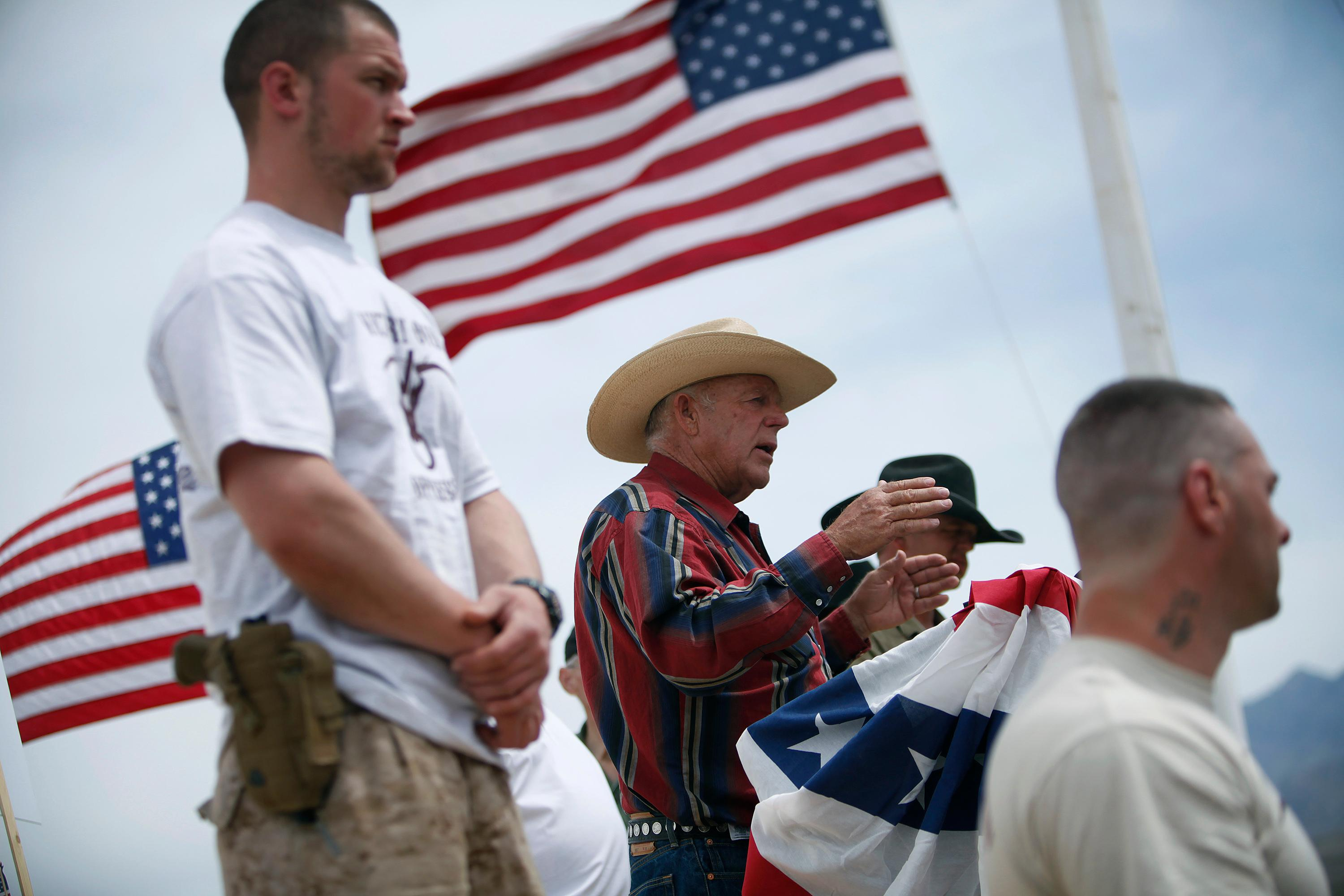FILE - In this April 18, 2014, file photo, flanked by armed supporters, rancher Cliven Bundy speaks at a protest camp near Bunkerville, Nev. A U.S. judge who declared a mistrial two weeks ago could on Monday, Jan. 8, 2018, kill the much-watched criminal prosecution of the Nevada rancher accused of leading an armed uprising against federal authorities in April 2014. Chief U.S. District Judge Gloria Navarro's decision in Las Vegas is sure to echo among states' rights advocates in Western states where the federal government controls vast expanses that some people want to remain unused and others want open to grazing, mining and oil and gas drilling. (John Locher/Las Vegas Review-Journal via AP, File)