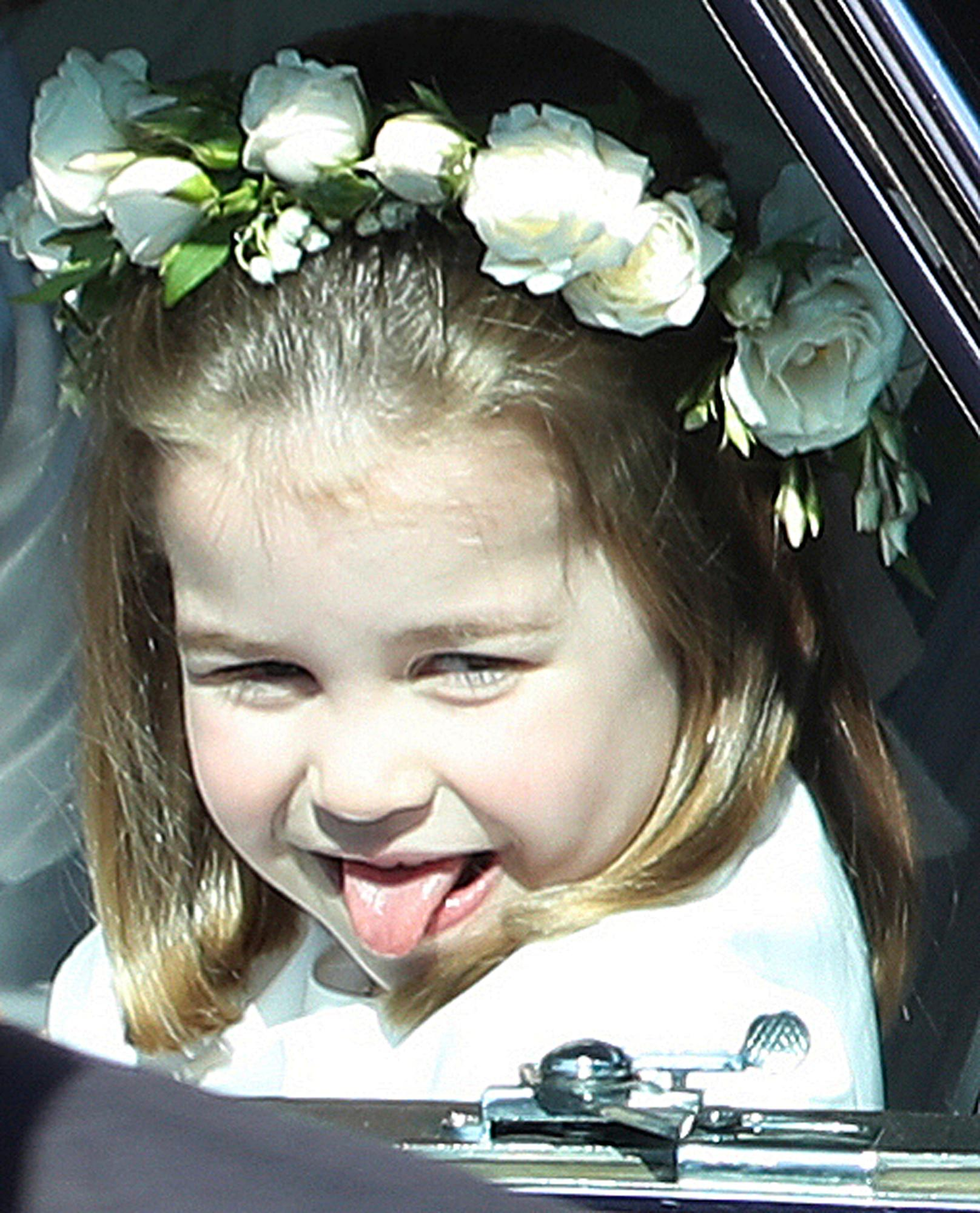 Princess Charlotte sticks out her tongue as she rides in a car to the wedding ceremony of Prince Harry and Meghan Markle at St. George's Chapel in Windsor Castle in Windsor, near London, England, Saturday, May 19, 2018. (Andrew Milligan/pool photo via AP)