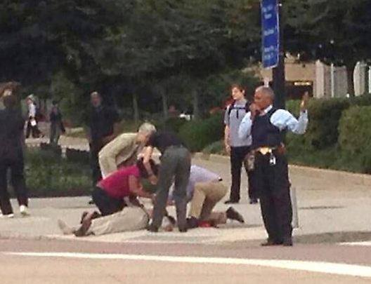People help a man on the ground at the Washington Navy Yard in Washington, Sept. 16, 2013. Police blocked off the area around the Navy Yard where a shooter opened fire, injuring several people.