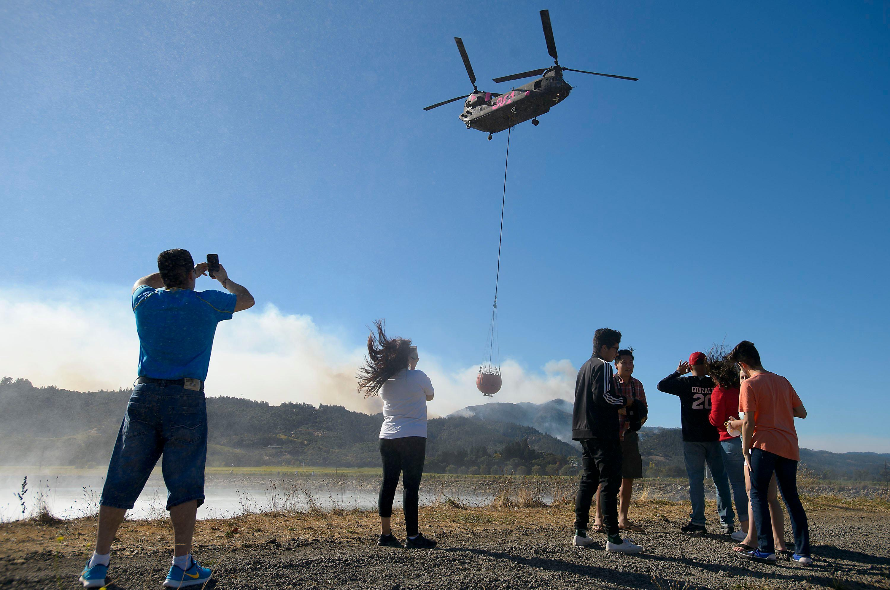 Hundreds of spectators watch as about a half-dozen helicopters fill their buckets with water from a reservoir on Dwyer Road in Yountville, Calif., on Saturday, Oct. 14, 2017. (Randall Benton /The Sacramento Bee via AP)