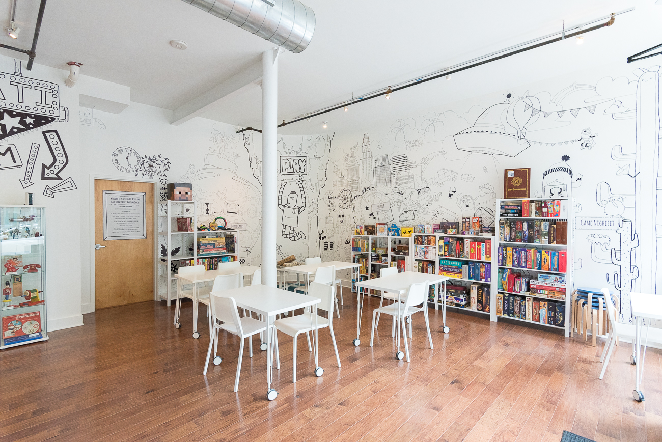 The Play Library has three sections: a vintage toy museum, an older kids/adults game section, and a younger kids game section (which is in a separate room from the other two sections). Board games and toys line the shelves in each area, with monochromatic murals painted along the walls. Soft astroturf covers window benches, a table is flanked by swing chairs, and the extra space offered by the new Main Street location lends itself well to dynamic programming. / Image: Phil Armstrong, Cincinnati Refined // Published: 6.7.19