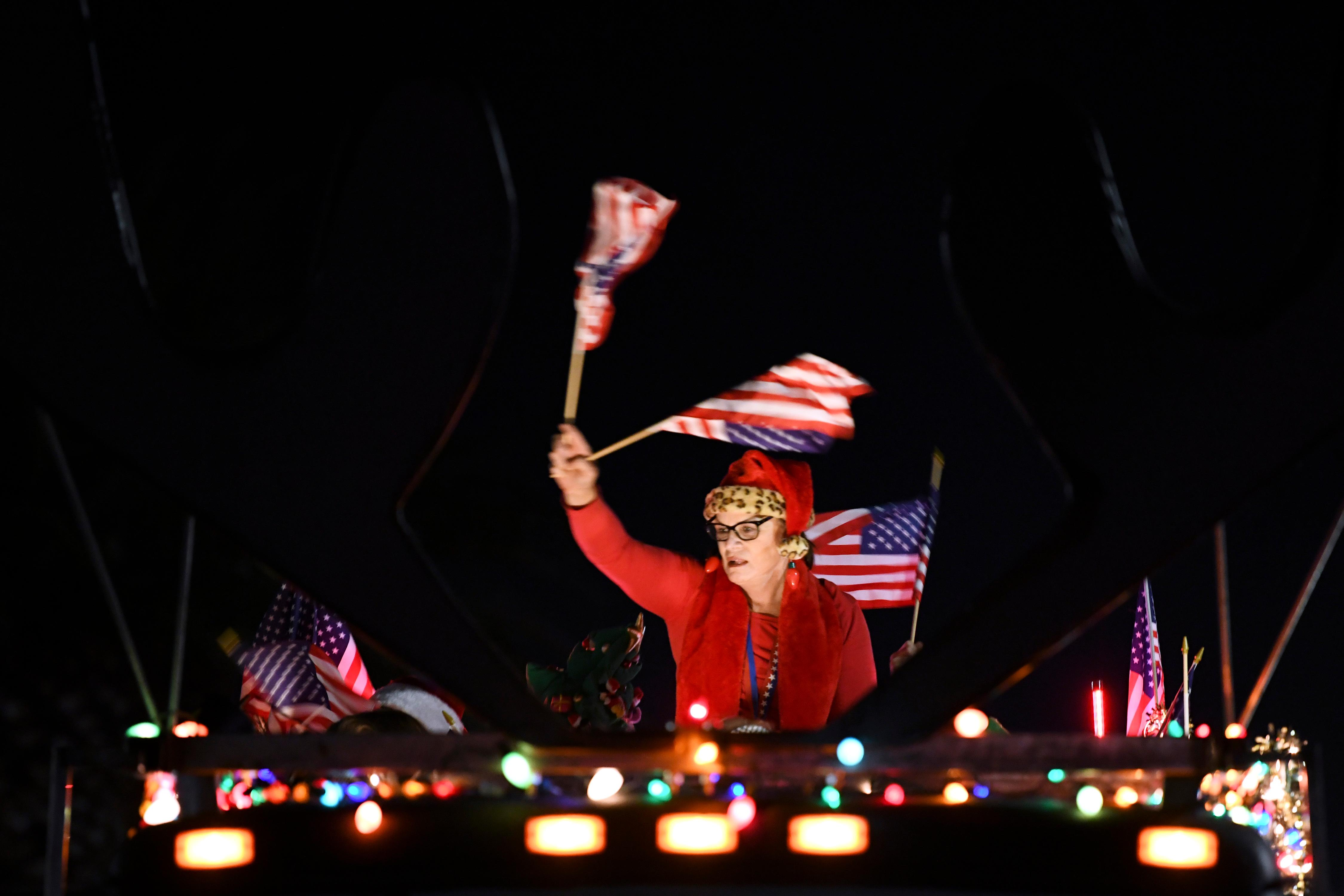 A woman waves United States flags during the Santa's Electric Parade Saturday, December 2, 2017, in Boulder City. [Sam Morris/Las Vegas News Bureau]