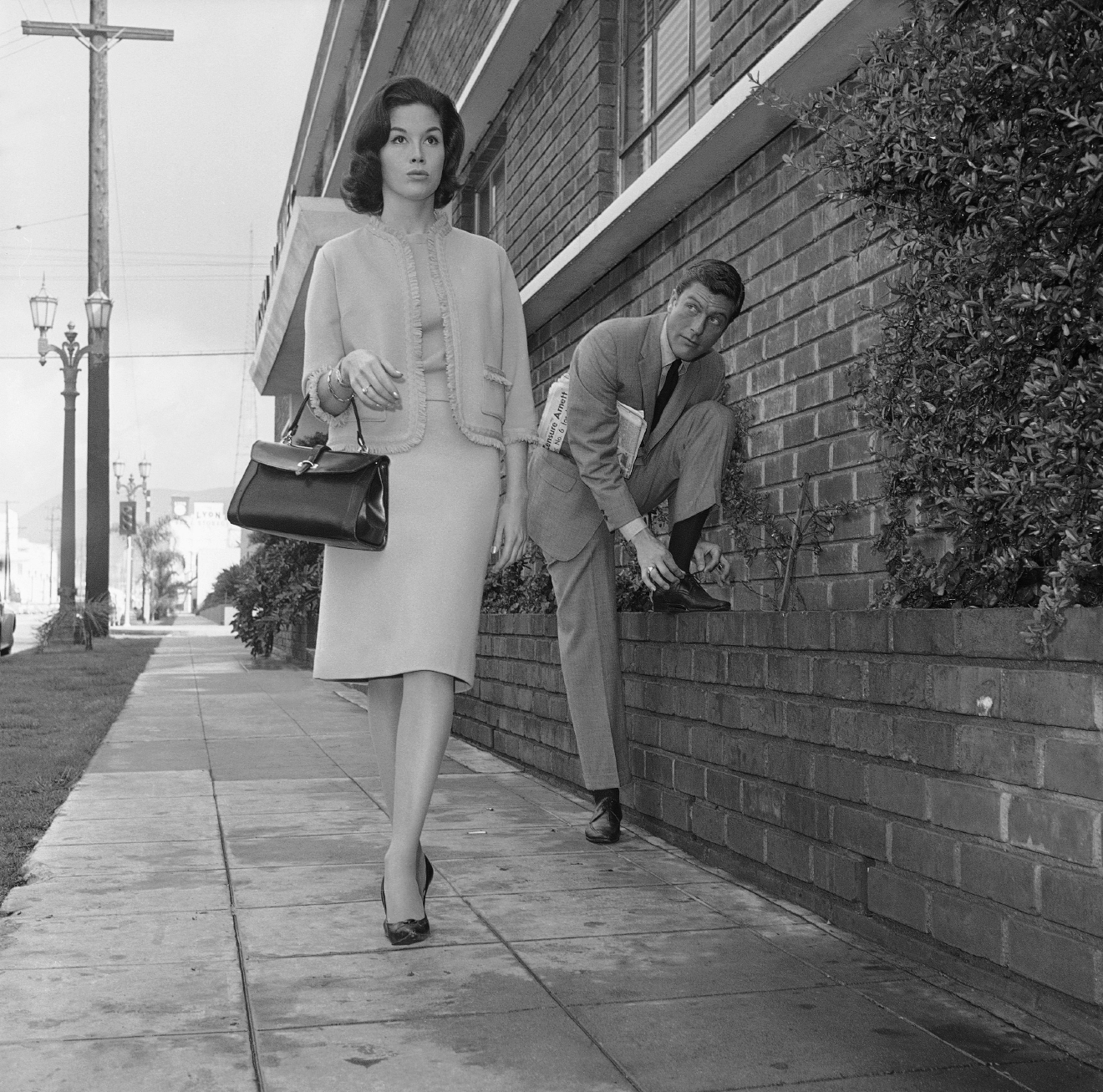 Actor Dick Van Dyke, right, looks on as actress Mary Tyler Moore walks by, Feb. 22, 1962, Los Angeles, Calif. (AP Photo/Don Brinn)