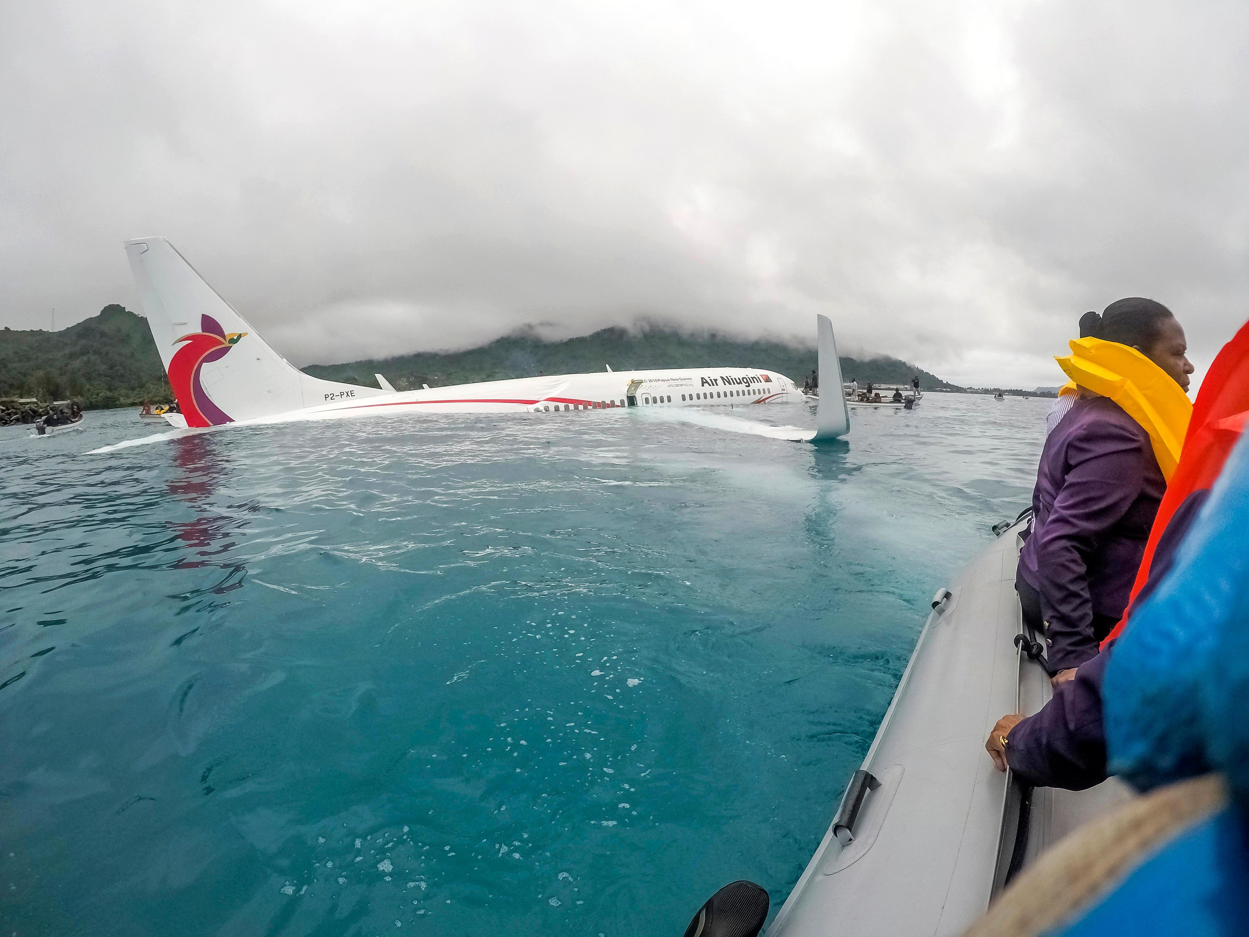 In this photo provided by the U.S. Navy, U.S. Navy Sailors from Underwater Construction Team (UCT) 2 assist local authorities in shuttling the passengers and crew of the Air Niugini flight to shore after the plane crashed into a lagoon on its approach to Chuuk International Airport in Micronesia., Friday, Sept. 28, 2018. All passengers and crew survived the plane's crash landing. (Lt. Zach Niezgodski/U.S. Navy via AP)