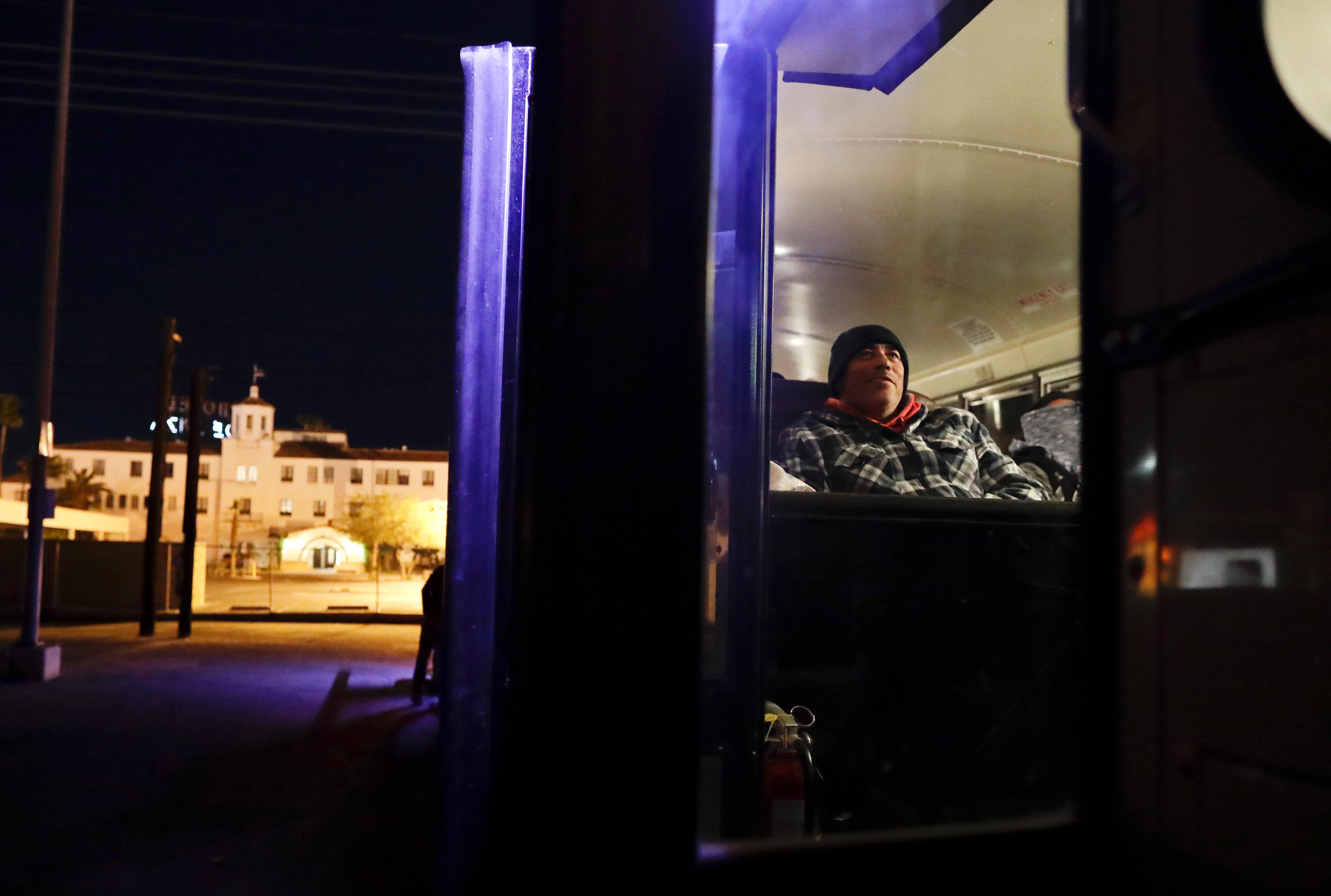 In this March 6, 2018 photo, farmworker Jose Angel Valenzuela rests as he waits before dawn in a bus that will take him and his crew from the border in Calexico, Calif, to a cabbage field ready for harvest outside of town. Valenzuela, who owns a house in Mexicali and is working his second harvest in Imperial Valley, earns more picking cabbage in an hour than he did in a day at a factory in Mexico. (AP Photo/Gregory Bull)