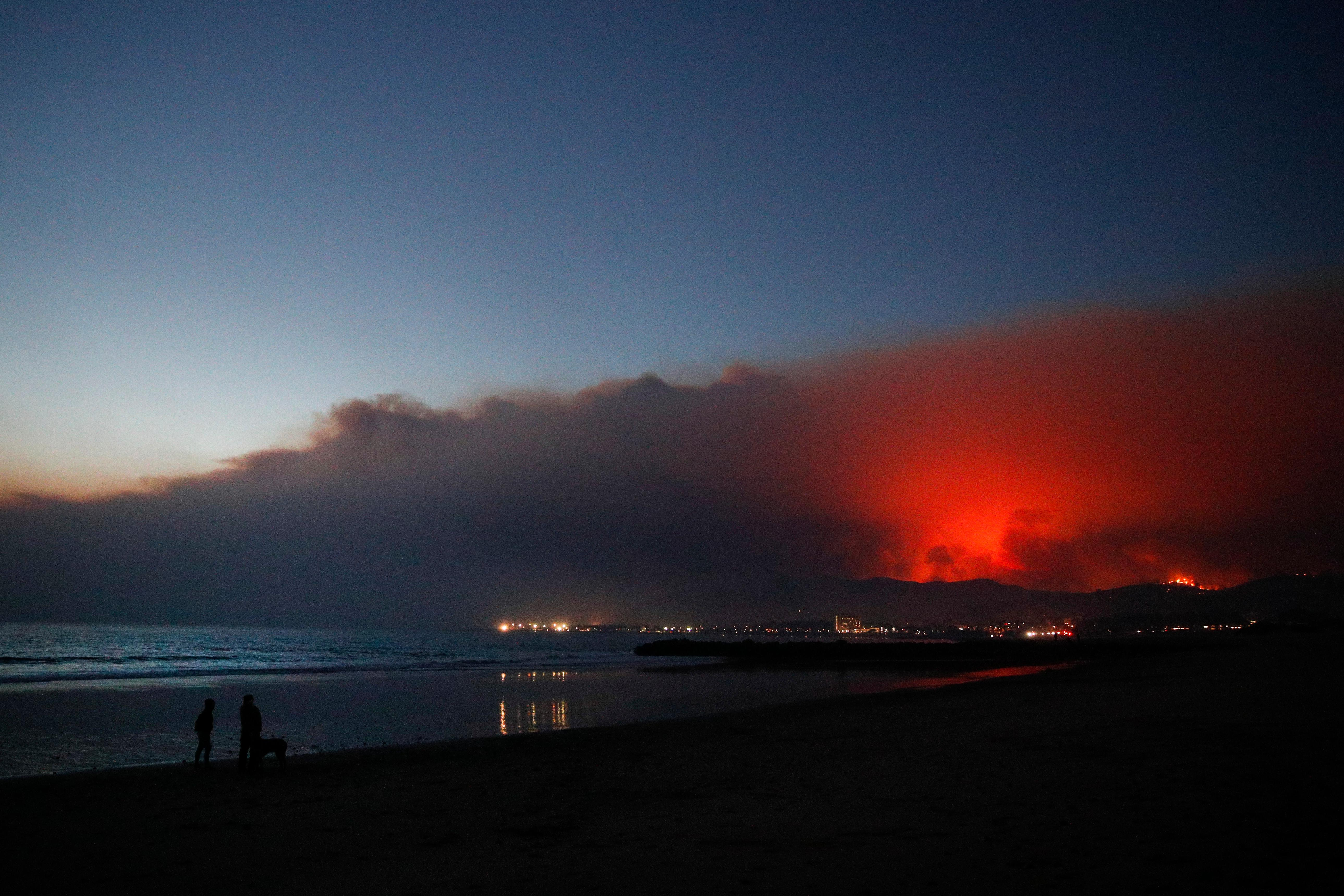 Two people walk along the beach with a dog as a wildfire burns in distance Tuesday, Dec. 5, 2017, in Ventura, Calif. Raked by ferocious Santa Ana winds, explosive wildfires northwest of Los Angeles and in the city's foothills burned a psychiatric hospital and scores of homes and other structures Tuesday and forced the evacuation of tens of thousands of people. (AP Photo/Jae C. Hong)