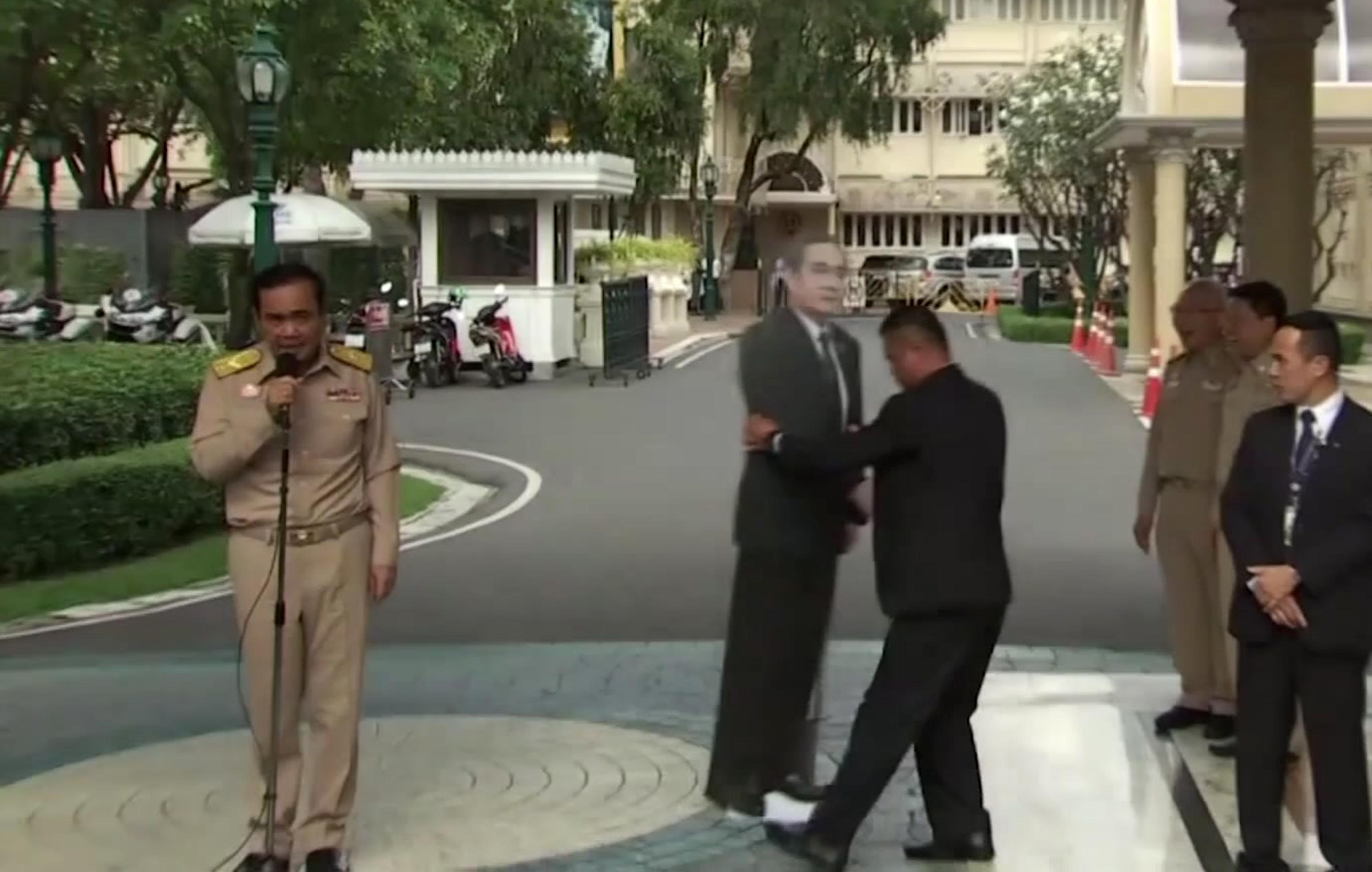 In this image from video, Thailand's Prime Minister Prayuth Chan-ocha, left, talks to the media as a life-sized cardboard cut-out figure of himself is carried into view by an aid, in Bangkok, Thailand, Monday Jan. 8, 2018. {&amp;nbsp;}(TPBS via AP)<p></p>