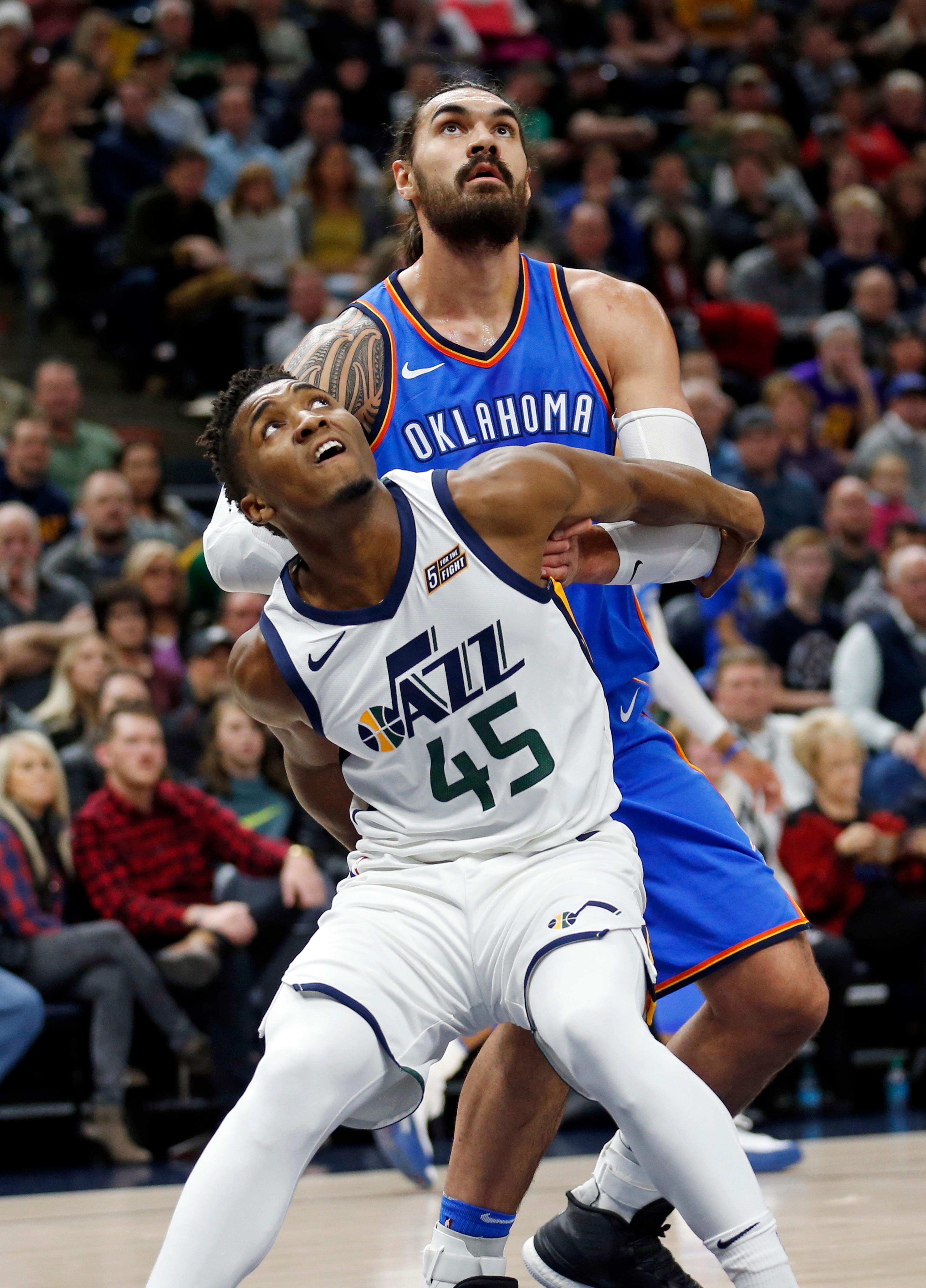 Utah Jazz guard Donovan Mitchell (45) and Oklahoma City Thunder center Steven Adams, right, battle under the boards for a rebound in the first half during an NBA basketball game Saturday, Dec. 23, 2017, in Salt Lake City. (AP Photo/Rick Bowmer)