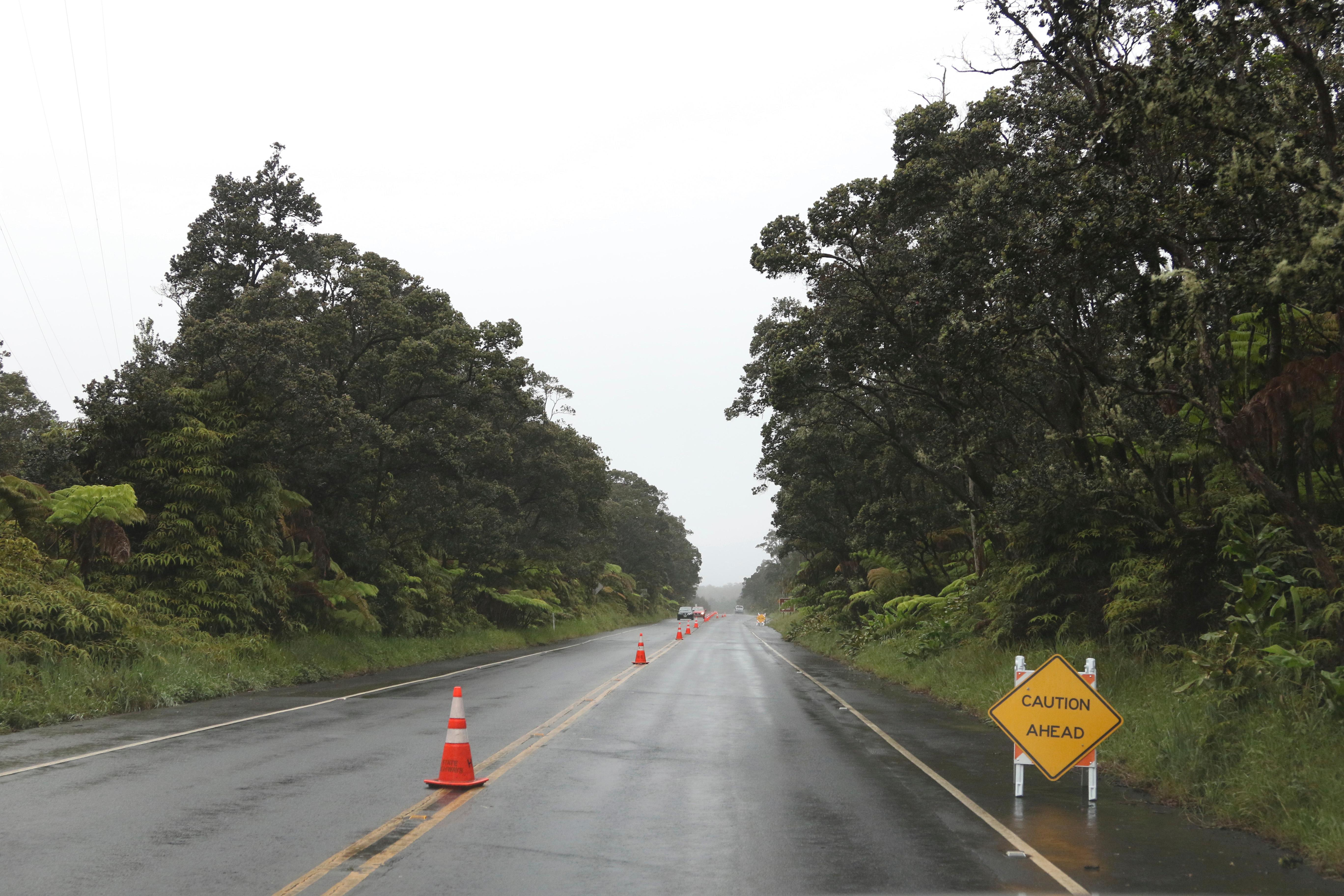 Cones and signs warn of cracks in the road near the entrance to Hawaii Volcanoes National Park, Thursday, May 17, 2018, near Volcano, Hawaii. (AP Photo/Caleb Jones)