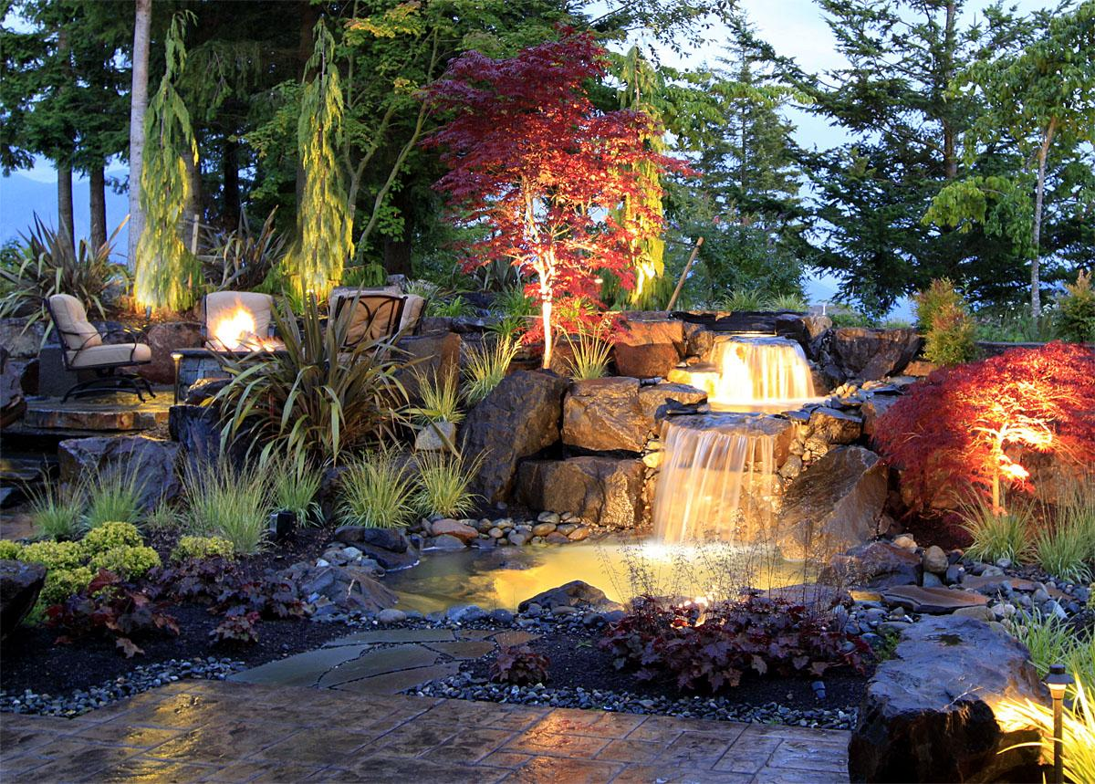 This Water Features project in Redmond was completed by Alderwood Landscaping, and aims to work the water into the backyard seamlessly, making it look as though the house was built around it.   (Image: Water Features / Porch.com)