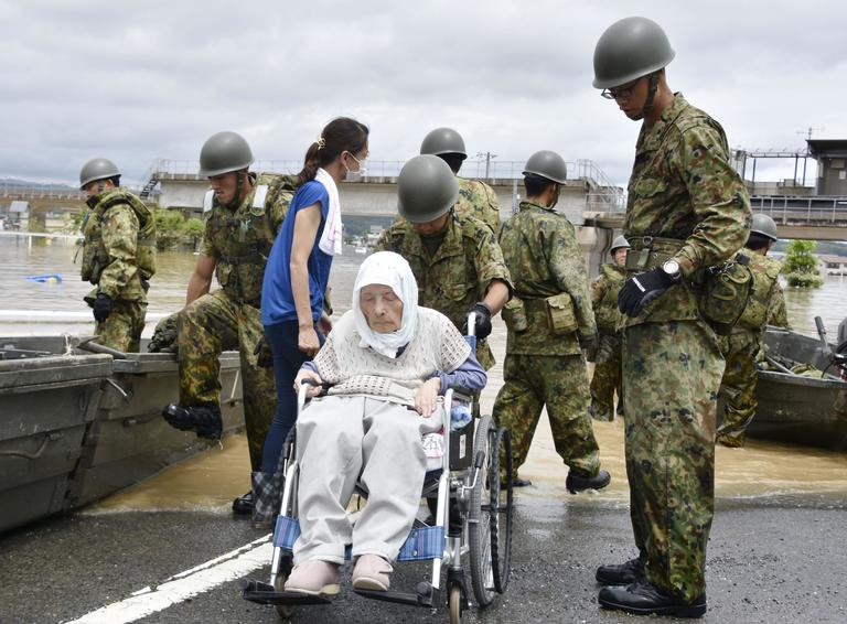 Elderly people is rescued as the city is flooded following heavy rain in Kurashiki city, Okayama prefecture, southwestern Japan, Sunday, July 8, 2018. Heavy rainfall hammered southern Japan for the third day, prompting new disaster warnings on Kyushu and Shikoku islands on Sunday. (Kyodo News via AP)