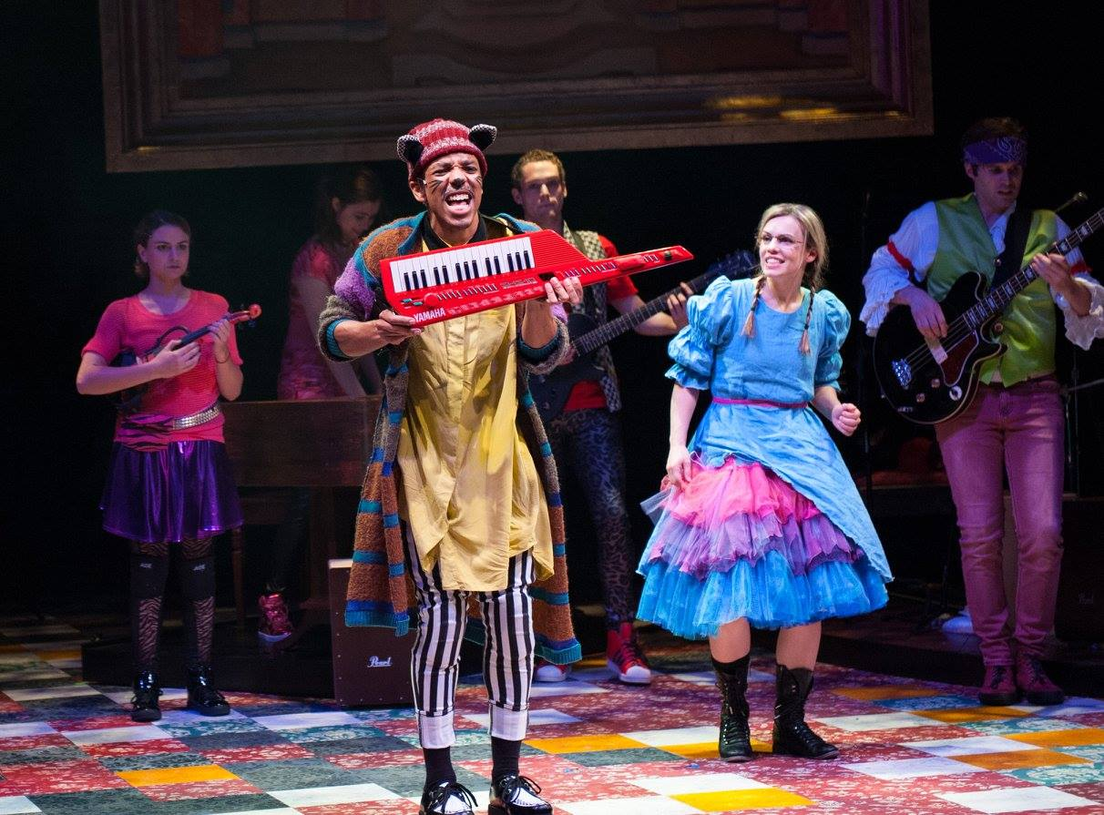 The Cheshire Cat shows off his keytar smile to Alice. (L-R: Hasani Allen, Erin Weaver, and Ensemble) Wonderland: Alice's Rock and Roll Adventure, Imagination Stage. (Image: Margot Schulman)