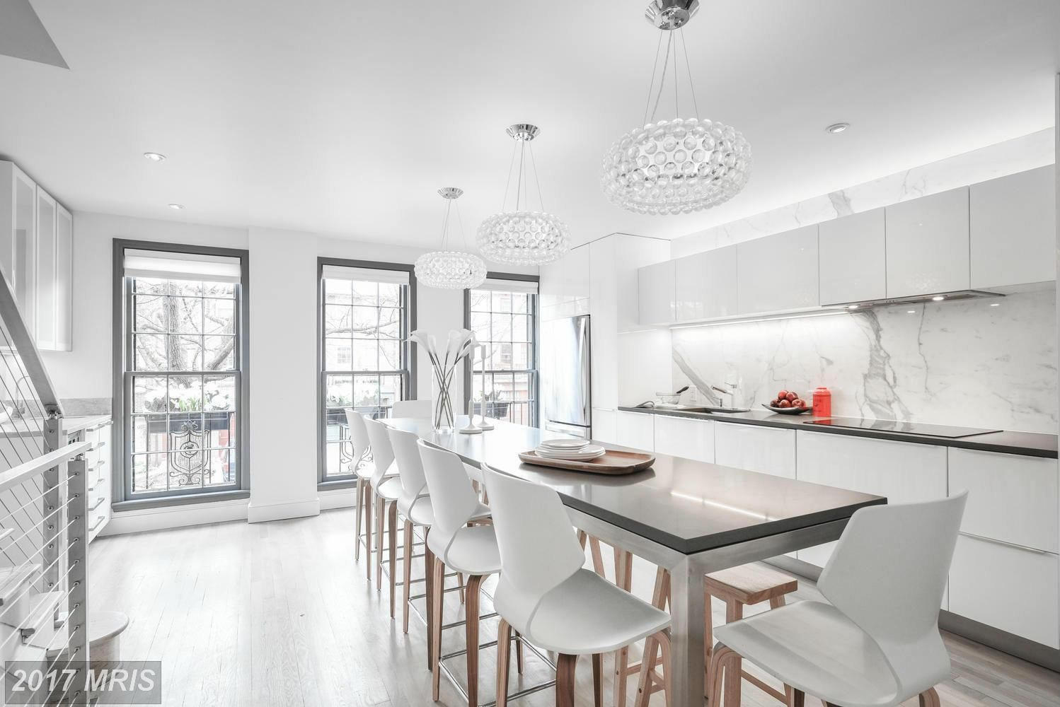 "It is quite rare to find a house that feels this modern, especially in a neighborhood as historic as Old Town Alexandria.  Built in the 1970s and renovated in 2015/2016 this townhouse has only been owned by two families in nearly 50 years! It is designed with family and easy entertaining in mind, which can be seen in the open floor plan of the kitchen and entire lower level. """"It is the cutting edge of a new trend in Old Town -- traditional styling is going by the wayside,"" says listing agent Sue Goodhart of McEnearney Associates. ""Contemporary, comfortable living is embodied in this renovation."" It combines the spaciousness of suburbia (check out the backyard patio!) with the amenities of city living -- it's less than a block from the waterfront where you can catch a water taxi to DC and is surrounded by dozens of upscale restaurants and shops to choose from. This two-bedroom/two-bath townhouse was listed for $1,049,000 but currently has a pending offer on it. Enjoy our gallery and visit mcenearney.com for more info on the lot. (Image: Courtesy McEnearney Associates)"
