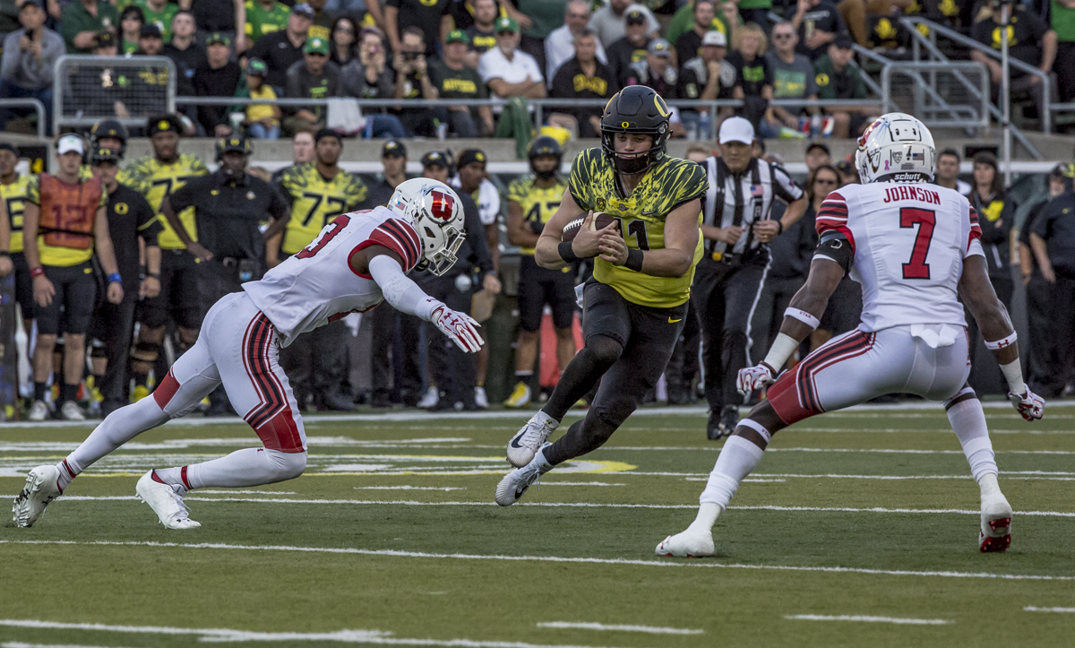 Oregon quarterback Braxton Burmeister (#11) runs on a quarterback keeper. The Oregon Ducks defeated the Utah Utes 41 to 20 during Oregon's homecoming game at Autzen Stadium on Saturday, October 28, 2017. Photo by Ben Lonergan, Oregon News Lab