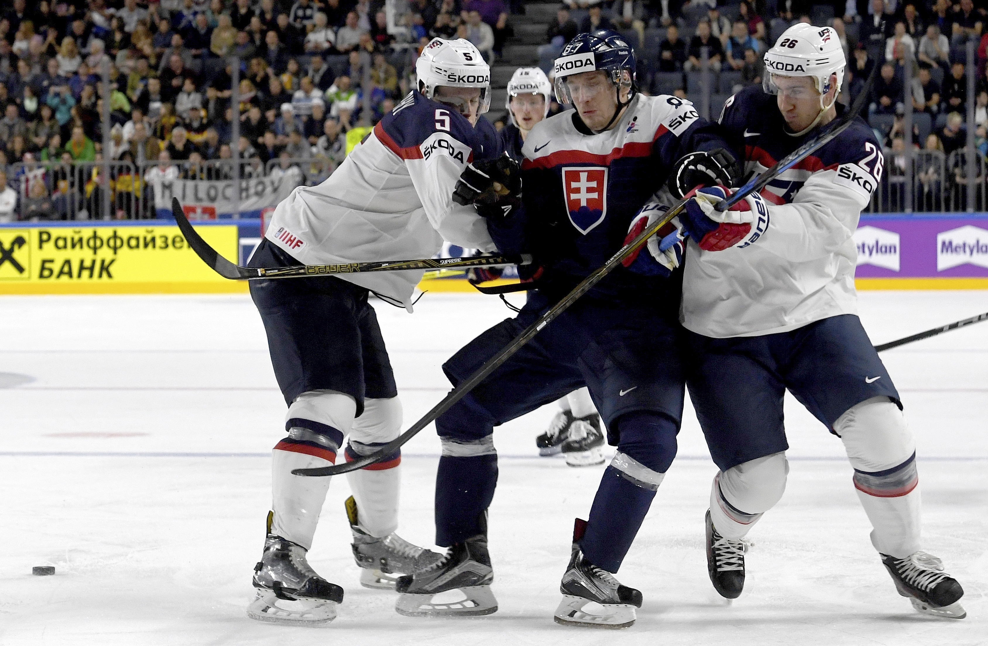 Slovakia's  Marcel Hascak , center, and US players  Connor Murphy, left, and Kevin Hayes challenge during a group A match between Slovakia and USA at the 2017 Hockey World Championships in the Lanxess Arena in  Cologne, Germany, Sunday, May 14, 2017.  (Monika Skolimowska/dpa via AP)
