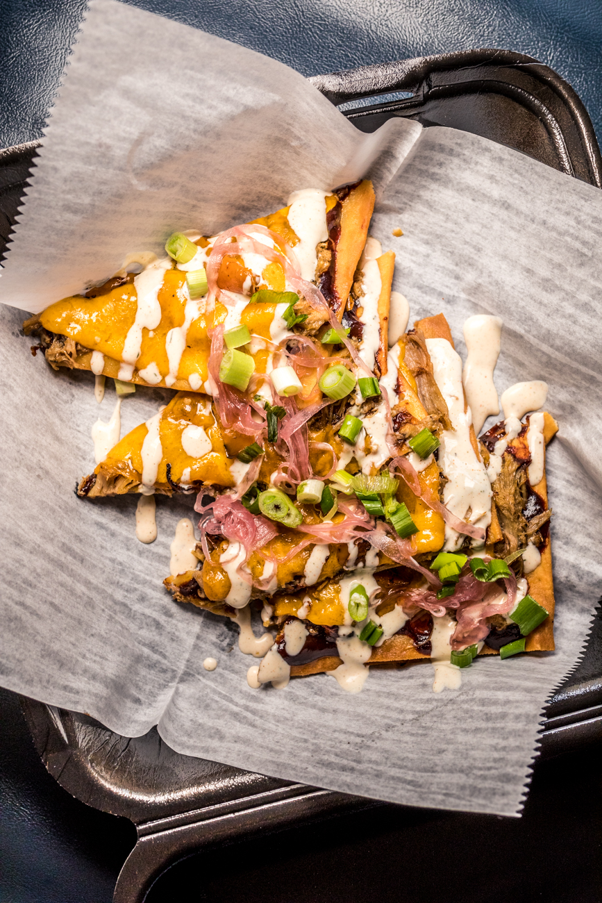 Pulled Pork Flatbread: pulled pork in bourbon BBQ with caramelized onion, sautéed peppers, and cheddar cheese drizzled with ranch and garnished with green onion / Image: Catherine Viox // Published: 5.18.20