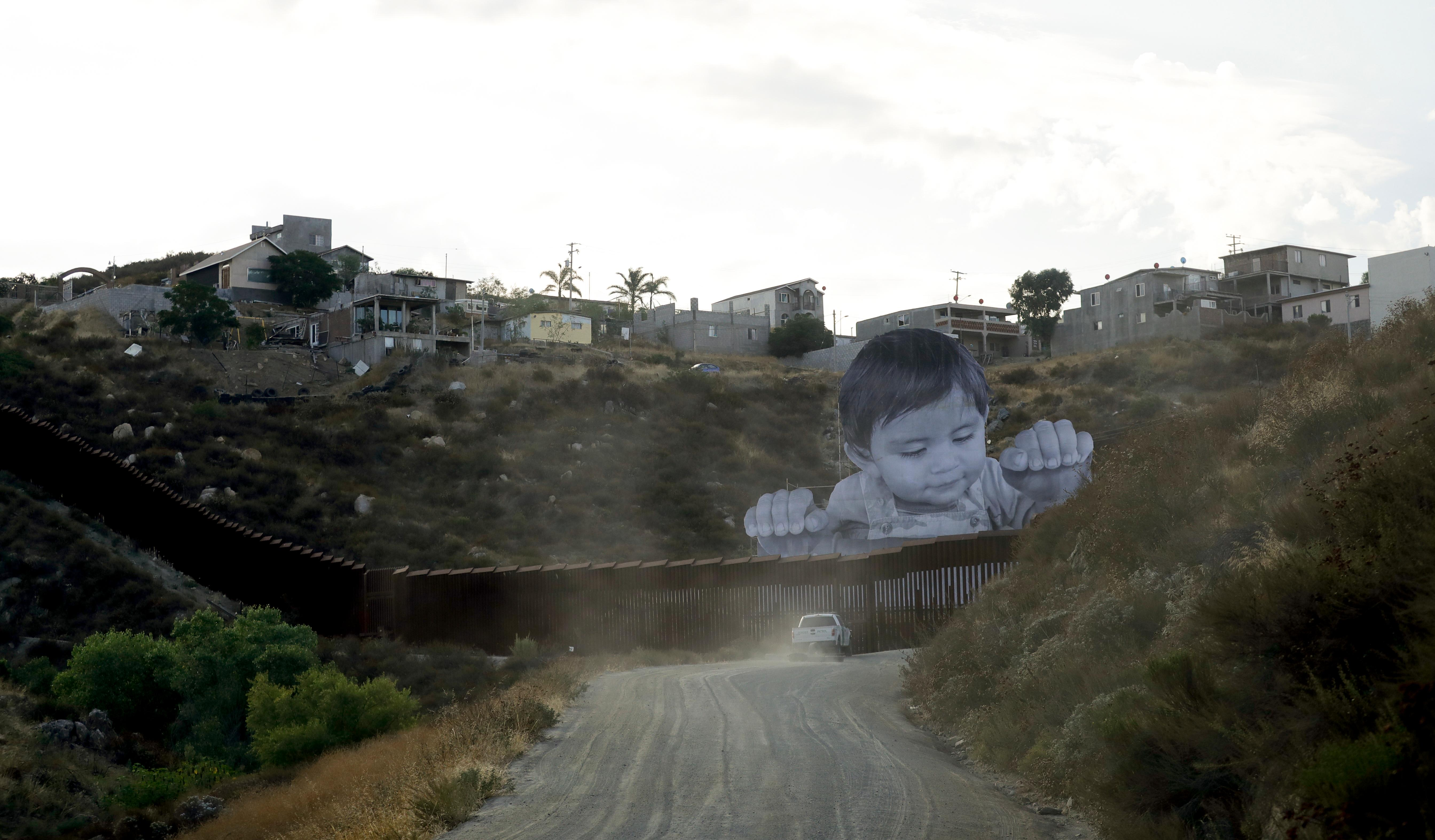 A Border Patrol vehicle drives in front of a mural in Tecate, Mexico, just beyond a border structure Friday, Sept. 8, 2017, in Tecate, Calif. A French artist aiming to prompt discussions about immigration erected a 65-foot-tall cut-out photo of a Mexican boy, pasting it to scaffolding built in Mexico. The image overlooks a section of wall on the California border and will be there for a month. (AP Photo/Gregory Bull)