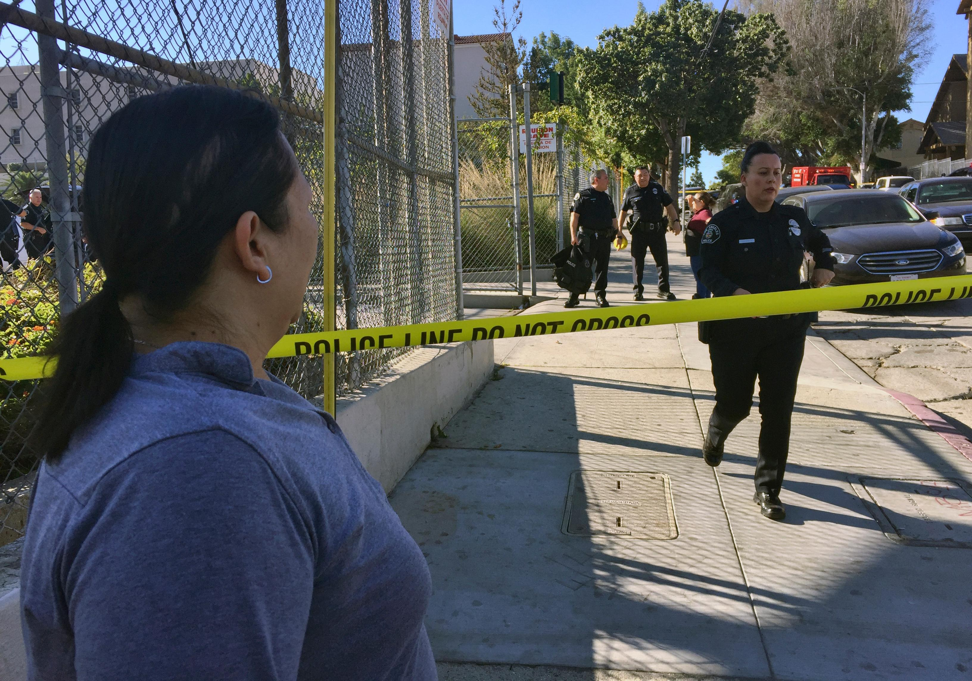 Gloria Echeverria watches as Los Angeles police officers close off a street where a shooting occurred at a middle school in Los Angeles on Thursday, Feb. 1, 2018. Two students were shot inside the middle school classroom Thursday morning and police arrested a female student suspect, authorities said. (AP Photo/Amanda Lee Myers)