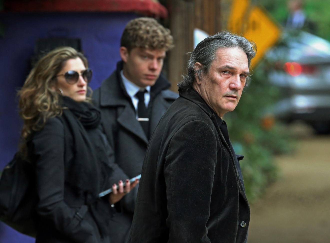 A man, center checks guests in as they arrive for a memorial service at the homes of Debbie Reynolds and Carrie Fisher in Los Angeles on Thursday, Jan. 5, 2017. A procession of stars arrived at the next door homes of Reynolds and her daughter Fisher on a gloomy Thursday afternoon amid reports that the private memorial was scheduled at the compound to mourn the late actresses. (AP Photo/Reed Saxon)
