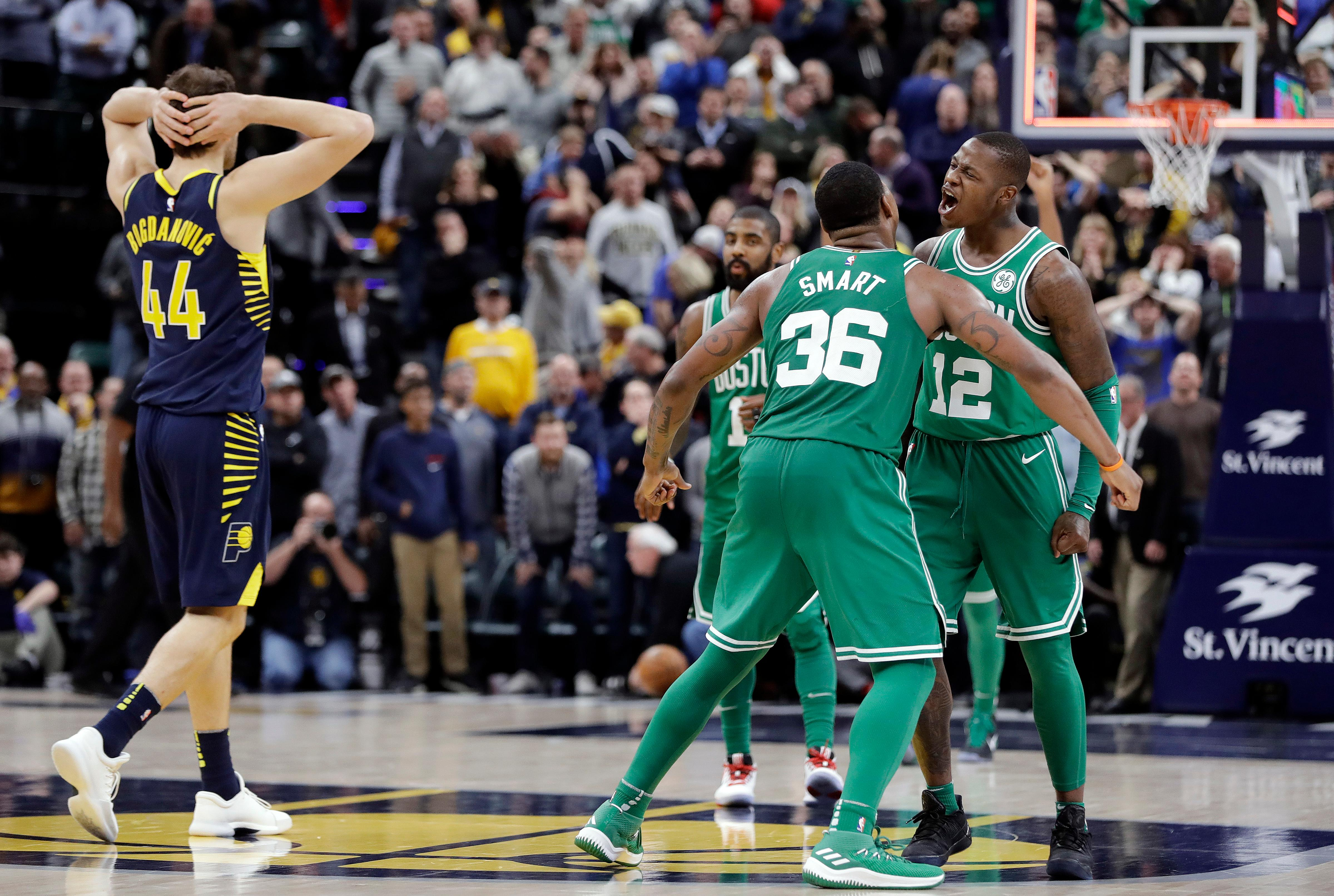 Boston Celtics' Terry Rozier (12) and Marcus Smart (36) celebrate as Indiana Pacers' Bojan Bogdanovic (44) watches after Boston defeated Indiana, 112-111, in an NBA basketball game, Monday, Dec. 18, 2017, in Indianapolis. (AP Photo/Darron Cummings)