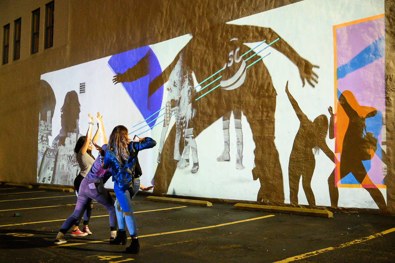 PICTURED NEIGHBORHOOD: Downtown / A funky interactive projection that uses people's silhouettes can be found on Main Street in a parking lot between 6th and 7th Streets. / Image: Phil Armstrong // Published: 10.12.19