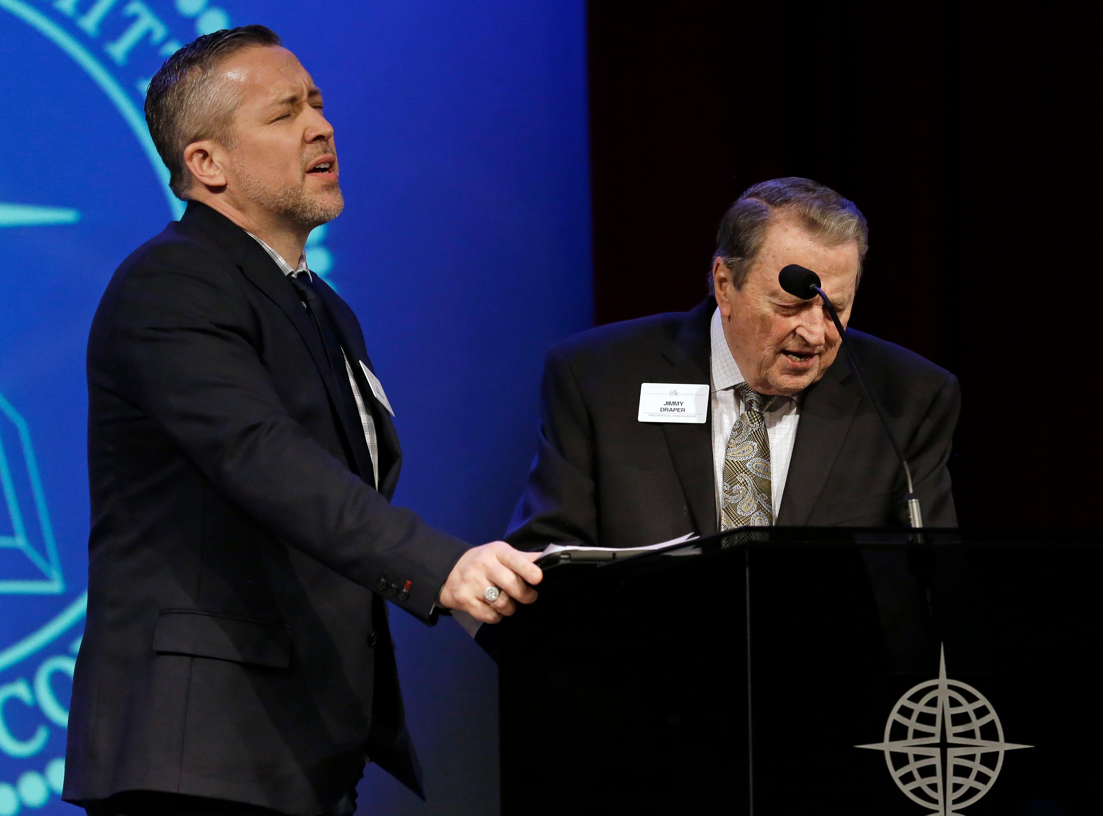 Southern Baptist Convention President J.D. Greear, left, prays with Jimmy Draper, right, a former denomination president, before Greear spoke to the denomination's executive committee Monday, Feb. 18, 2019, in Nashville, Tenn. Just days after a newspaper investigation revealed hundreds of sexual abuse cases by Southern Baptist ministers and lay leaders over the past two decades, Greear spoke about plans to address the problem. (AP Photo/Mark Humphrey)
