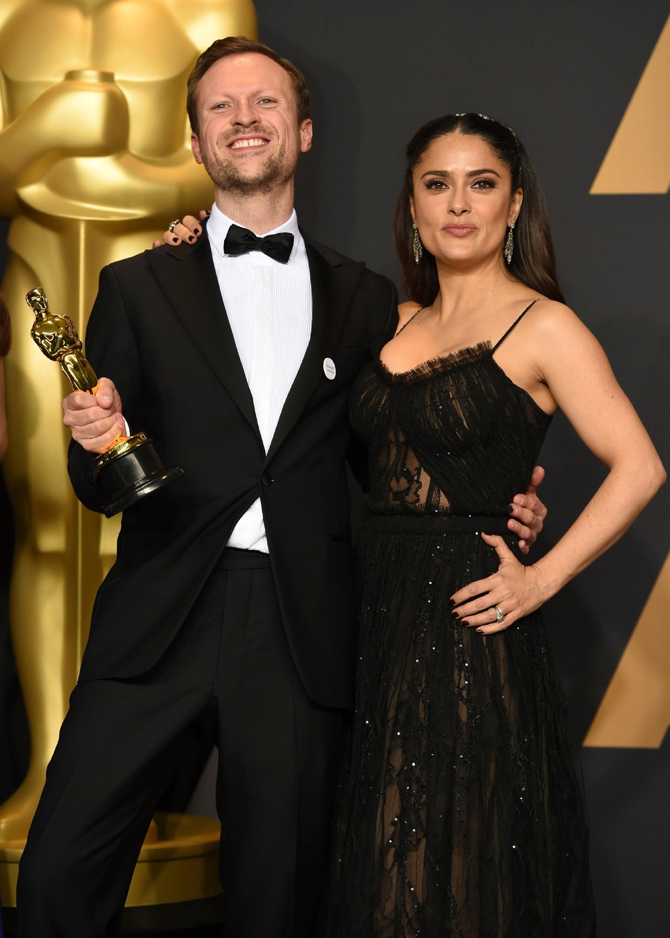 "Orlando von Einsiedel, left, winner of the award for for best documentary short subject for ""The White Helmets"", poses in the press room with Salma Hayek at the Oscars on Sunday, Feb. 26, 2017, at the Dolby Theatre in Los Angeles. (Photo by Jordan Strauss/Invision/AP)"