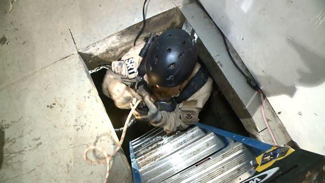 Agents climb into the tunnel where 8 tons of marijuana and 325 pounds of cocaine were seized