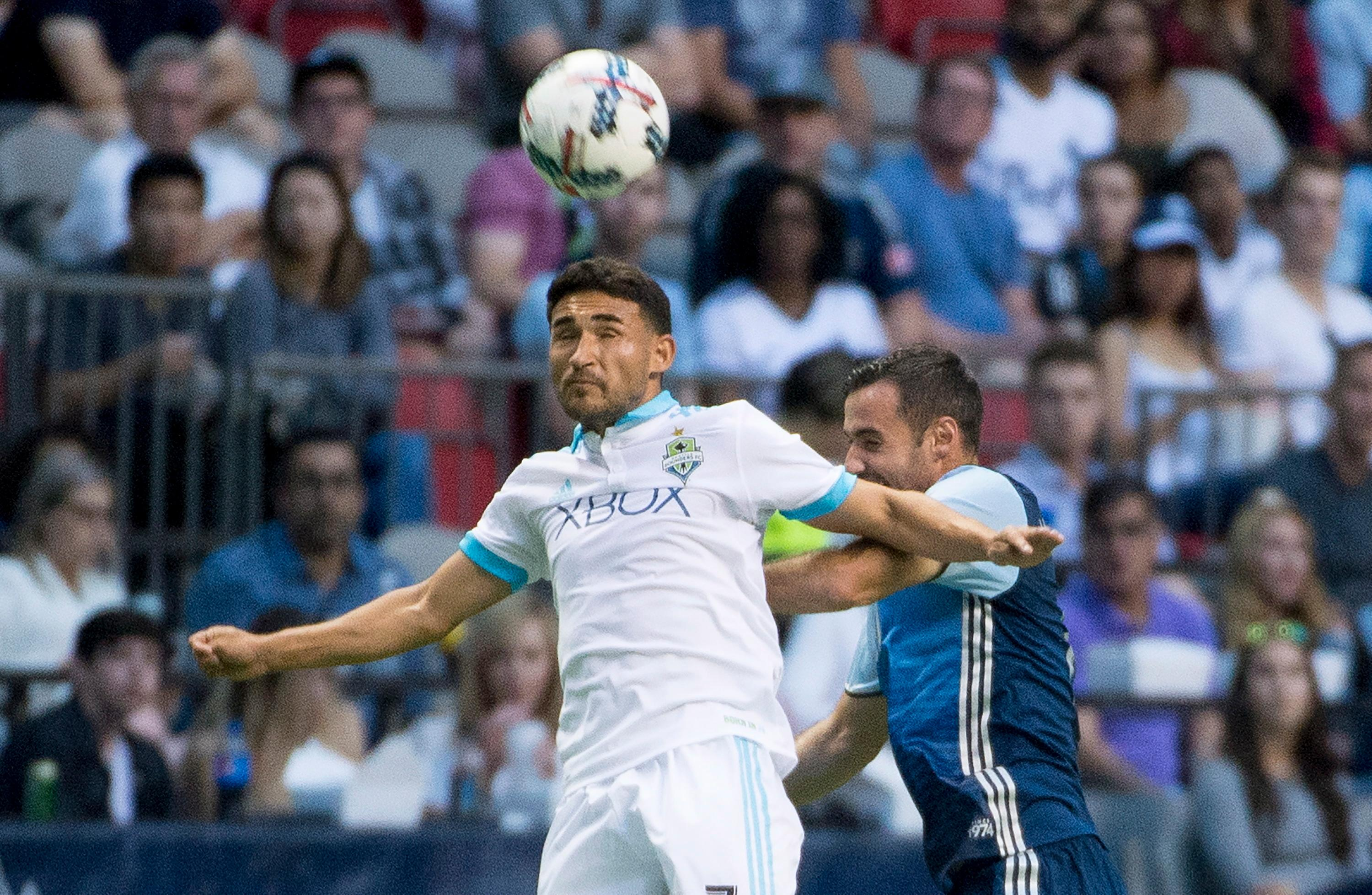 Seattle Sounders midfielder Cristian Roldan heads the ball next to Vancouver Whitecaps midfielder Andrew Jacobson (8) during the first half of an MLS soccer match Wednesday, Aug. 23, 2017, in Vancouver, British Columbia. (Jonathan Hayward/The Canadian Press via AP)