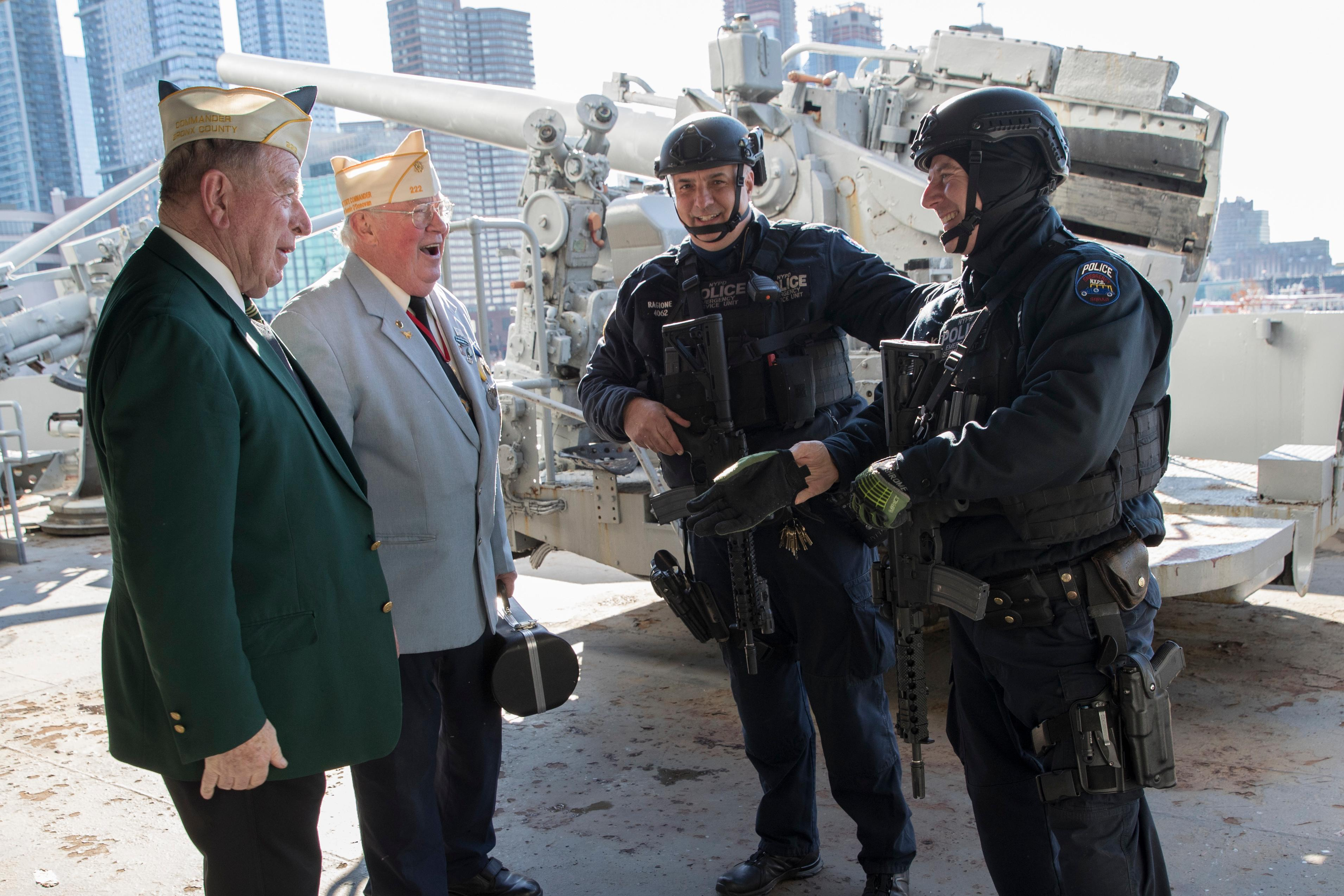 Veterans John Dunleavy, left, and Jim Mullarkey, second from left, speak to heavily armed police officers during a ceremony commemorating the 76th anniversary of the Dec. 7, 1941 Japanese attack on Pearl Harbor, Thursday, Dec. 7, 2017, on board the Intrepid Sea, Air & Space Museum in New York. (AP Photo/Mary Altaffer)