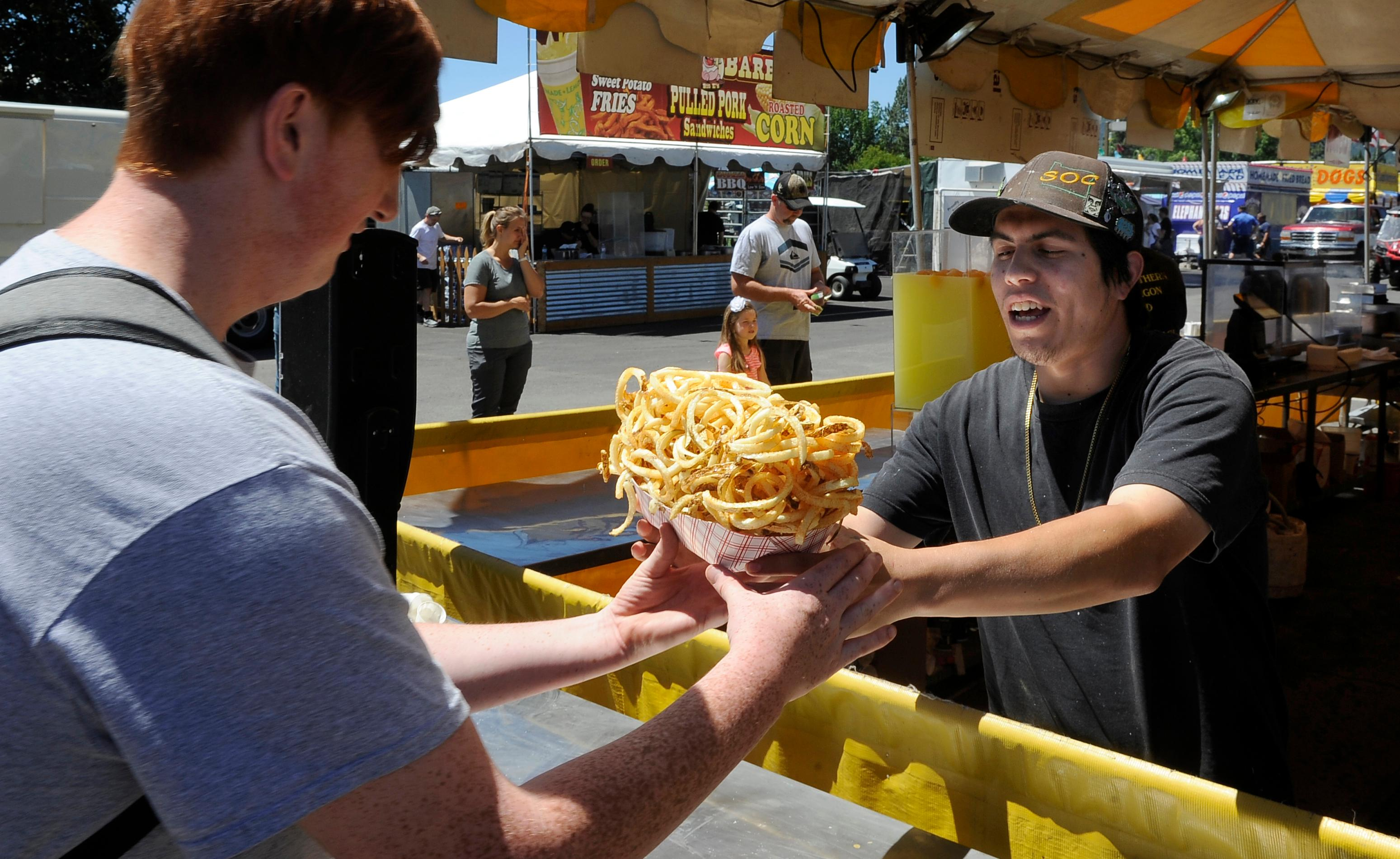 Andy Atkinson / Mail Tribune<br>Armando Barreto hands a basket of curly fries to Austin Harvey at the Jackson County Fair Tuesday.