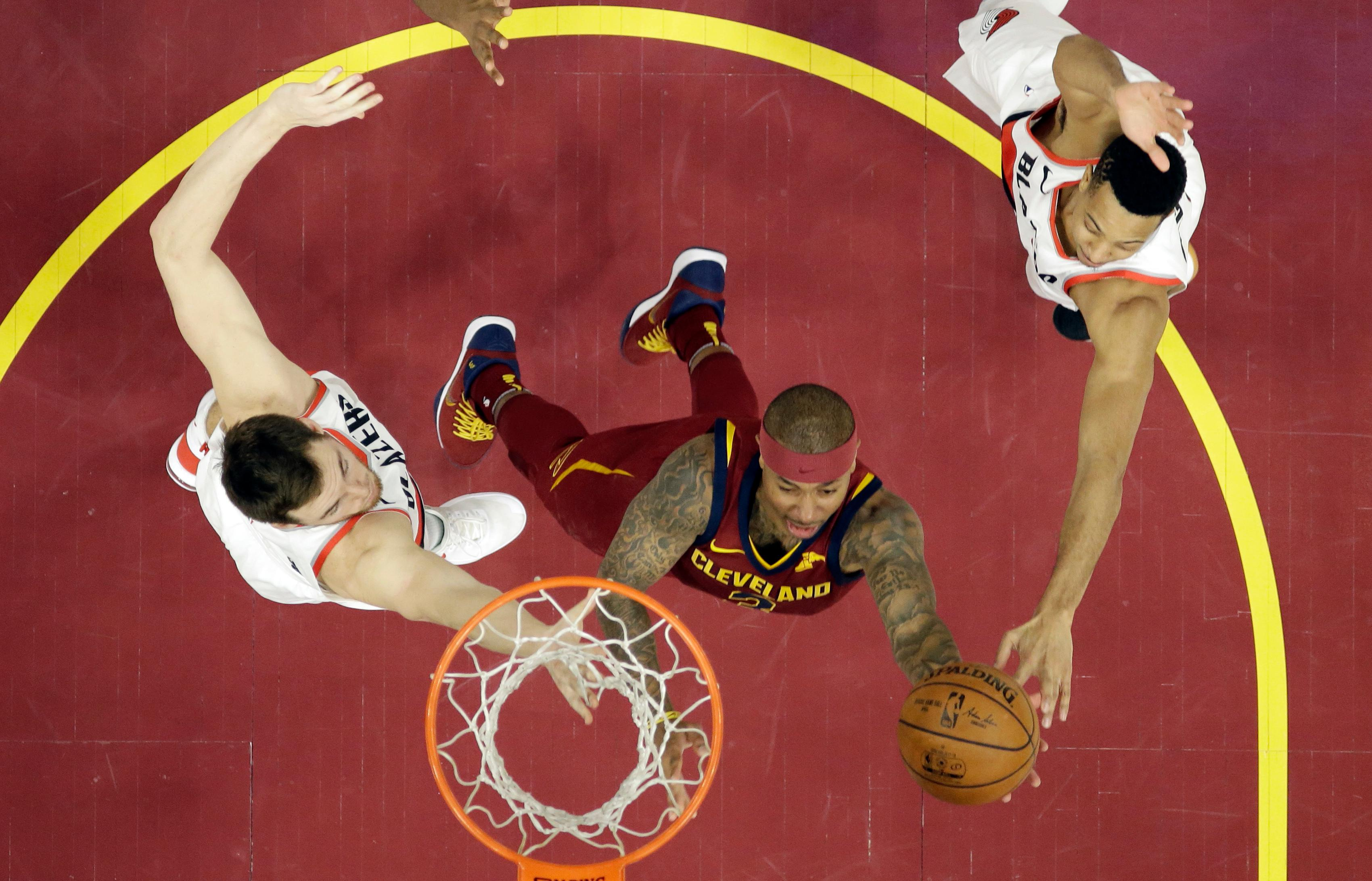 Cleveland Cavaliers' Isaiah Thomas, center, drives to the basket against Portland Trail Blazers' Pat Connaughton, left, and CJ McCollum in the second half of an NBA basketball game, Tuesday, Jan. 2, 2018, in Cleveland. The Cavaliers won 127-110. (AP Photo/Tony Dejak)