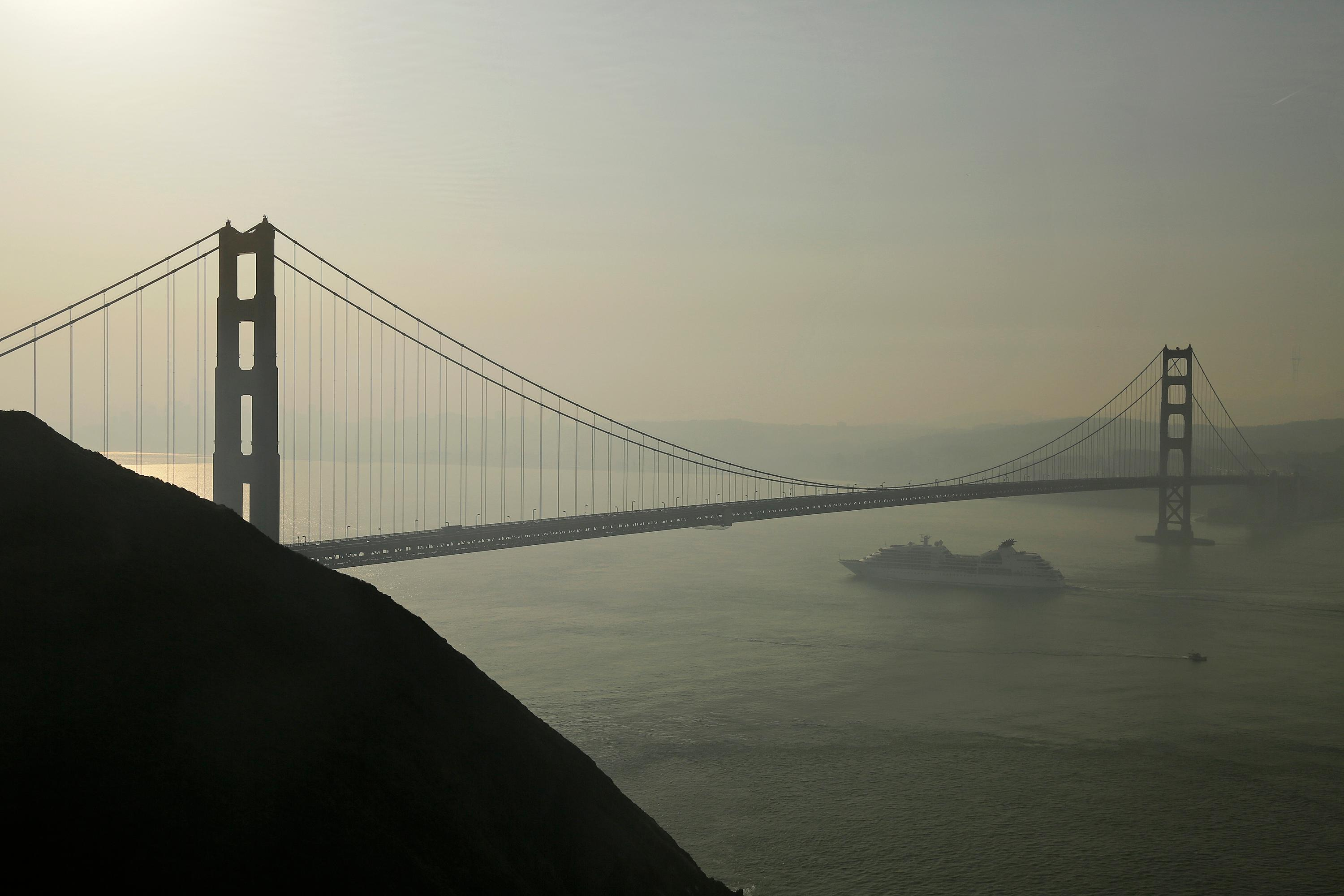 A cruise ship passes beneath the Golden Gate Bridge as smoke from wildfires blankets the San Francisco skyline Tuesday, Oct. 10, 2017, in this view near Sausalito, Calif. An onslaught of wildfires across a wide swath of Northern California broke out almost simultaneously then grew exponentially, swallowing up properties from wineries to trailer parks and tearing through both tiny rural towns and urban subdivisions. (AP Photo/Eric Risberg)