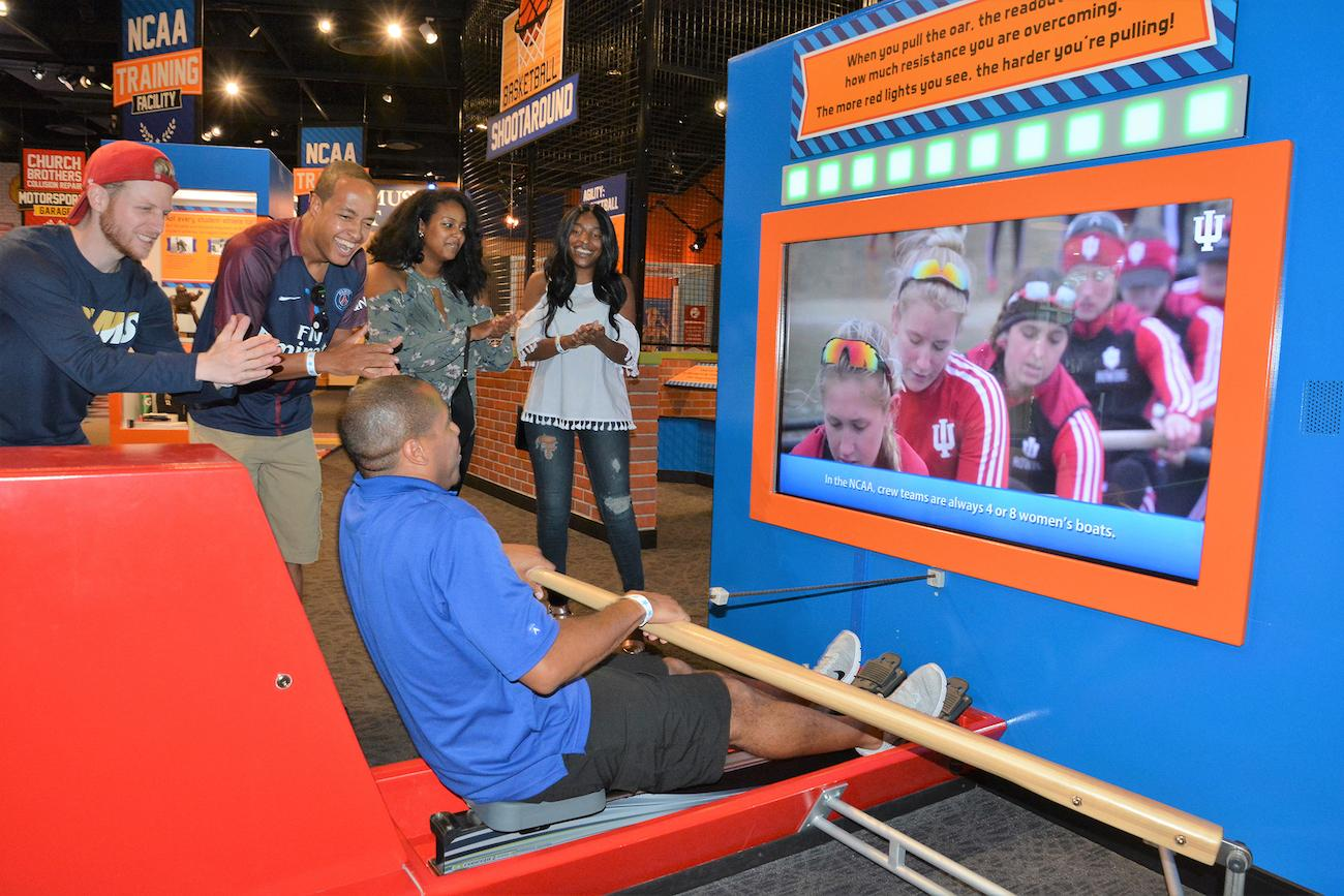 The NCAA Sports Legends Training Facility is one of three indoor exhibits in the museum's Riley Children's Health Sports Legends Experience. Practice sticking a landing from a gymnastics beam, test your basketball skills, try a hockey goal-blocker challenge, listen to famous moments in NCAA history, or (as the picture shows) work together in a crew rowing simulator. / Image courtesy of Children's Museum of Indianapolis // Published: 4.2.19