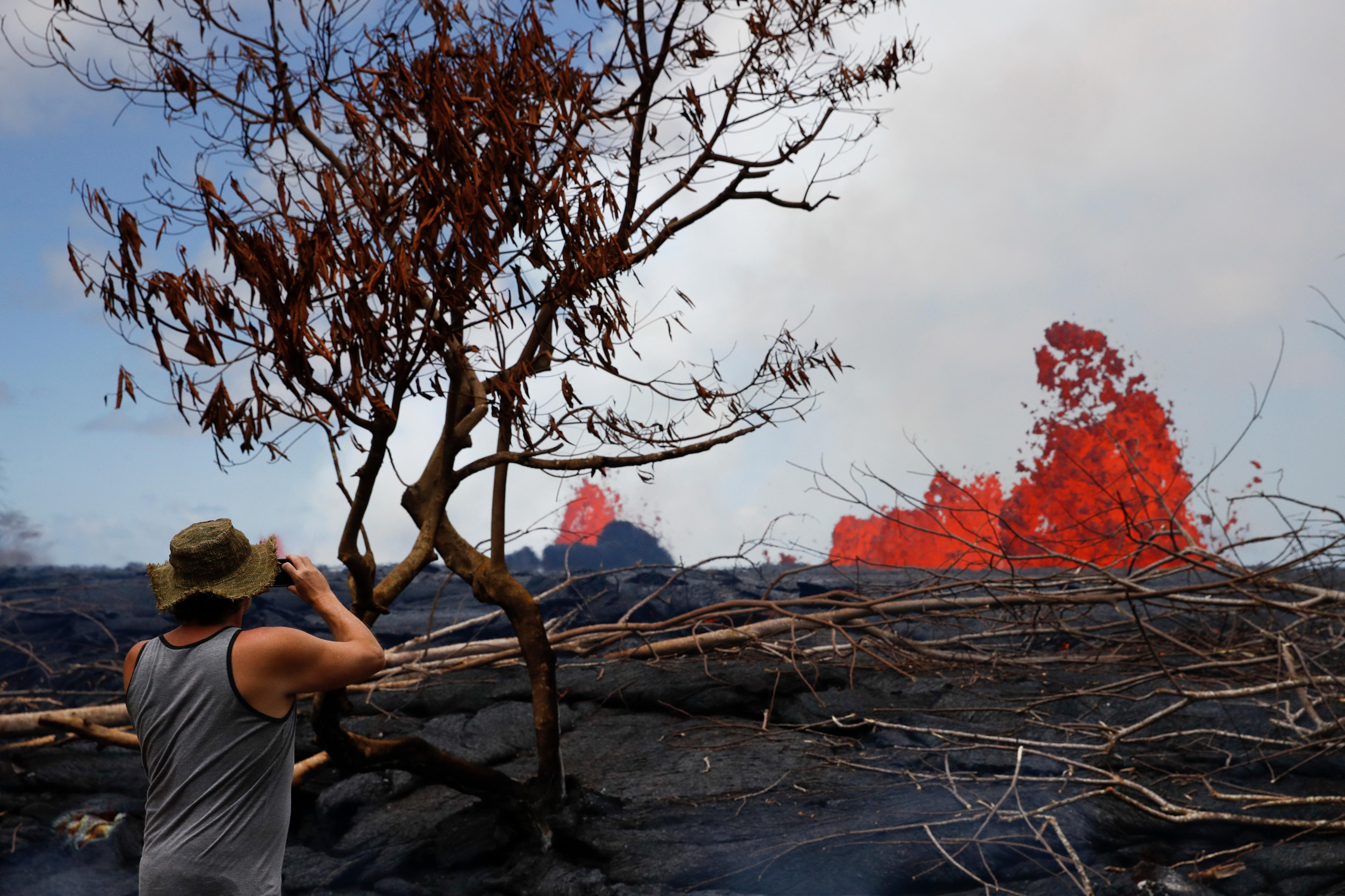 A resident takes photos as fissures spew lava in the Leilani Estates subdivision near Pahoa, Hawaii, Tuesday, May 22, 2018. Authorities were racing Tuesday to close off production wells at a geothermal plant threatened by a lava flow from Kilauea volcano on Hawaii's Big Island. (AP Photo/Jae C. Hong)