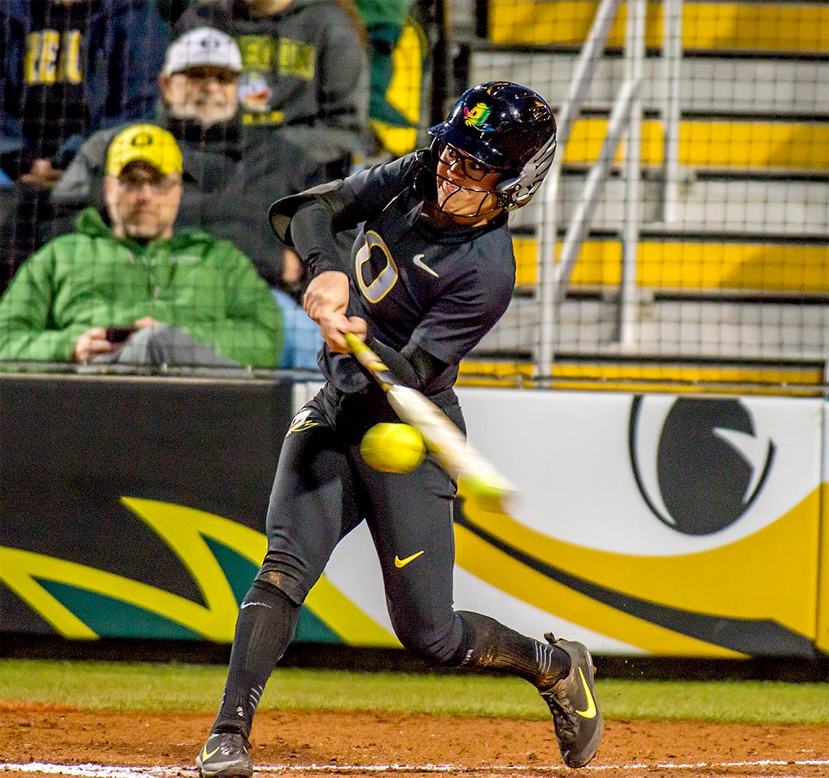 The Duck's Danica Mercado (#2) connects with the ball. In Game Two of a three-game series, the University of Oregon Ducks softball team defeated the University of Washington Huskies 4-1 Friday night in Jane Sanders Stadium. Danica Mercado (#2), Alexis Mack (#10) and Mia Camuso (#7) all scored in the win, Mack twice. The Ducks play the Huskies for the tie breaker on Saturday with the first pitch at noon. Photo by August Frank, Oregon News Lab