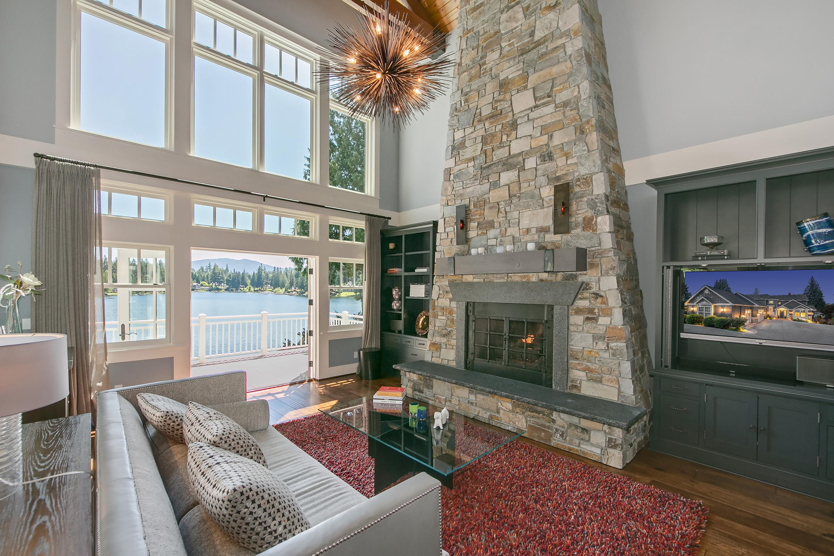 The great room on the main level stars a soaring fireplace made of river rock and three French doors that open onto an expansive patio.