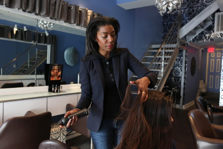 Shun Pittman, the owner and founder of Corps d'Elite salon on U Street, says you don't have to tuck a flat iron in your bag to look put-together when the hats come off - she swears by a combo of products and an ounce of prevention. (Amanda Andrade-Rhoades/DC Refined)