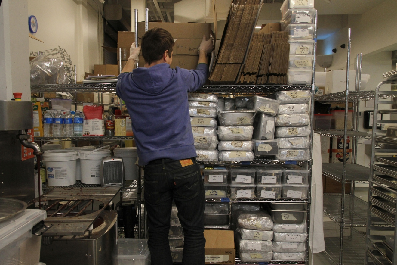 Adam crawls up storage racks to grab ingredients. Undone Chocolate is currently sold in 100 stores, half of which are local, and he hopes to eventually move into a more spacious facility with an attached store. (Image: Amanda Andrade-Rhoades/ DC Refined)
