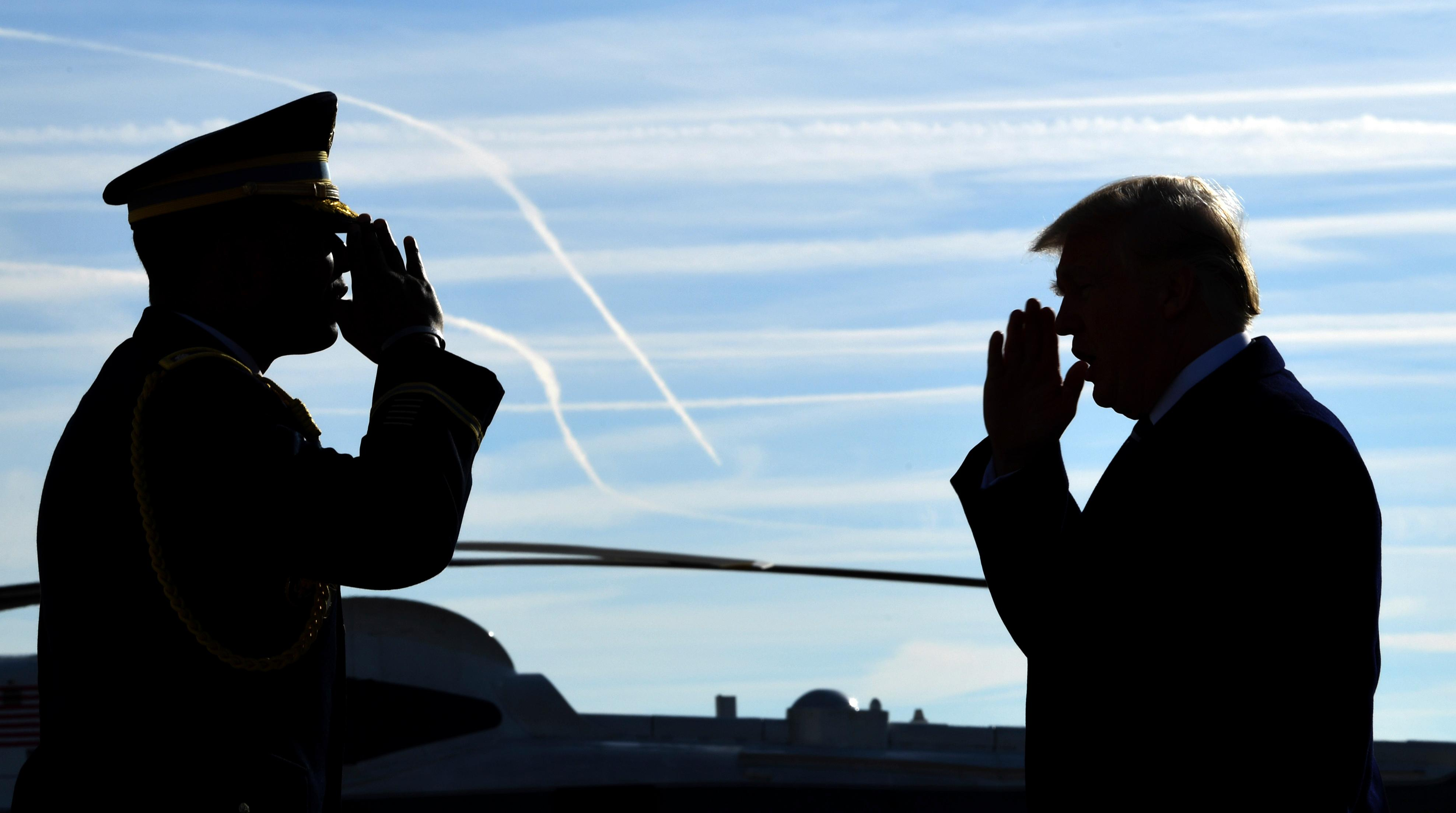 President Donald Trump is greeted with a salute as he walks down the steps of Air Force One at John F. Kennedy International Airport in New York, Saturday, Dec. 2, 2017. Trump is in New York to attend a series of fundraisers. (AP Photo/Susan Walsh)