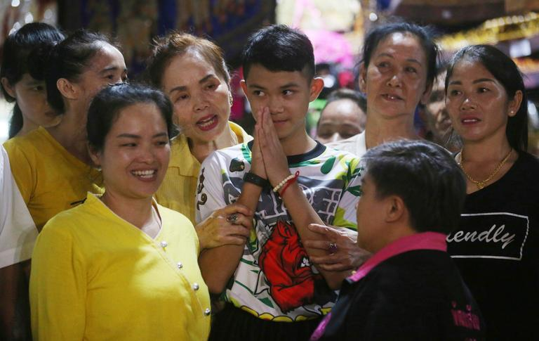 Relatives of Duangpetch Promthep, center, one of the boys rescued from the flooded cave in northern Thailand, greet him as he arrives home in the Mae Sai district, Chiang Rai province, northern Thailand, Wednesday, July 18, 2018. The 12 boys and their soccer coach rescued from a cave in northern Thailand left the hospital where they had been recuperating and appeared at a news conference Wednesday, saying the ordeal made them stronger and taught them not to live carelessly. (AP Photo/Sakchai Lalit)