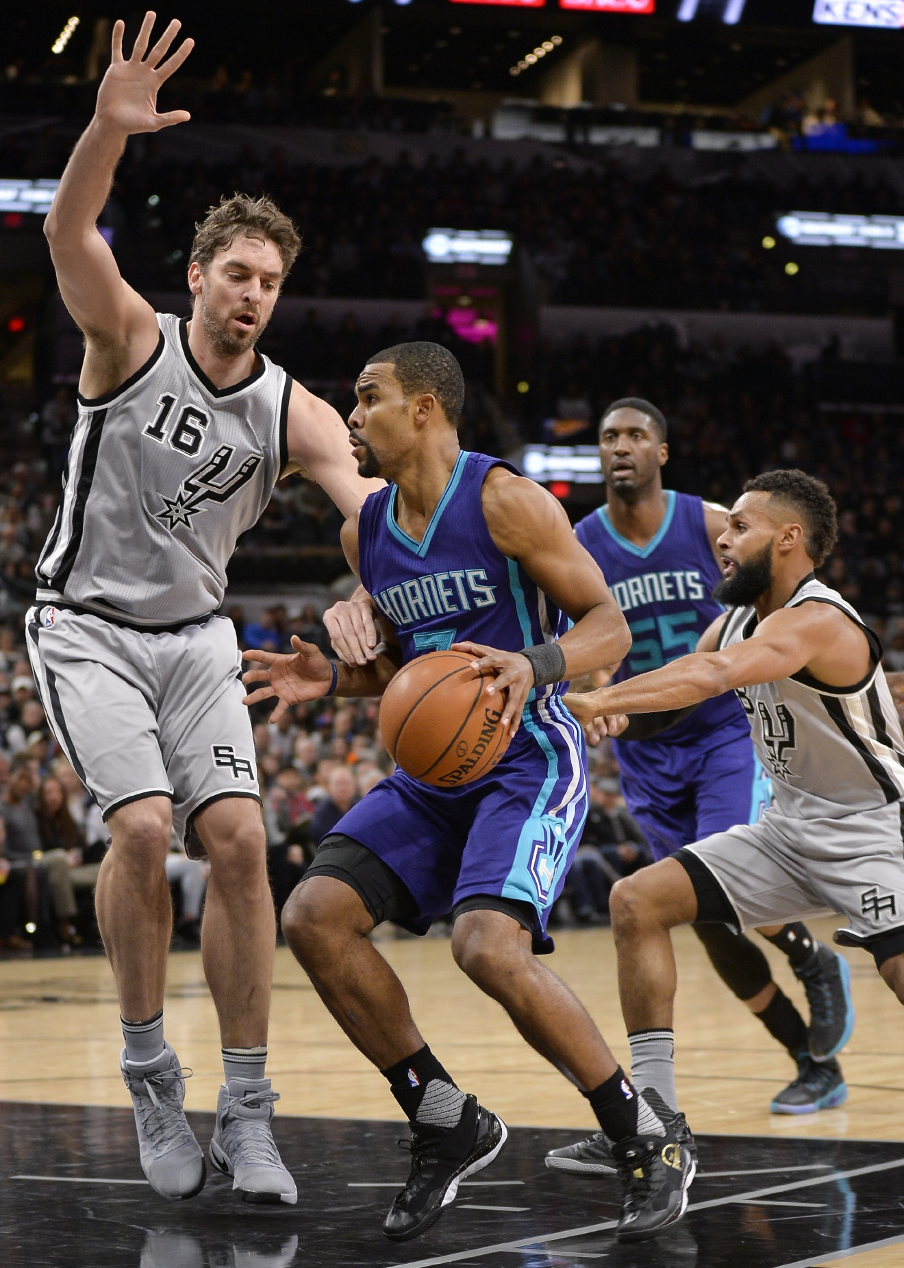 Charlotte Hornets guard Ramon Sessions, second from left, drives the lane against San Antonio Spurs center Pau Gasol, left, of Spain, and Spurs guard Patty Mills, right, of Australia, as Hornets center Roy Hibbert looks on during the first half of an NBA basketball game, Saturday, Jan. 7, 2017, in San Antonio. (AP Photo/Darren Abate)