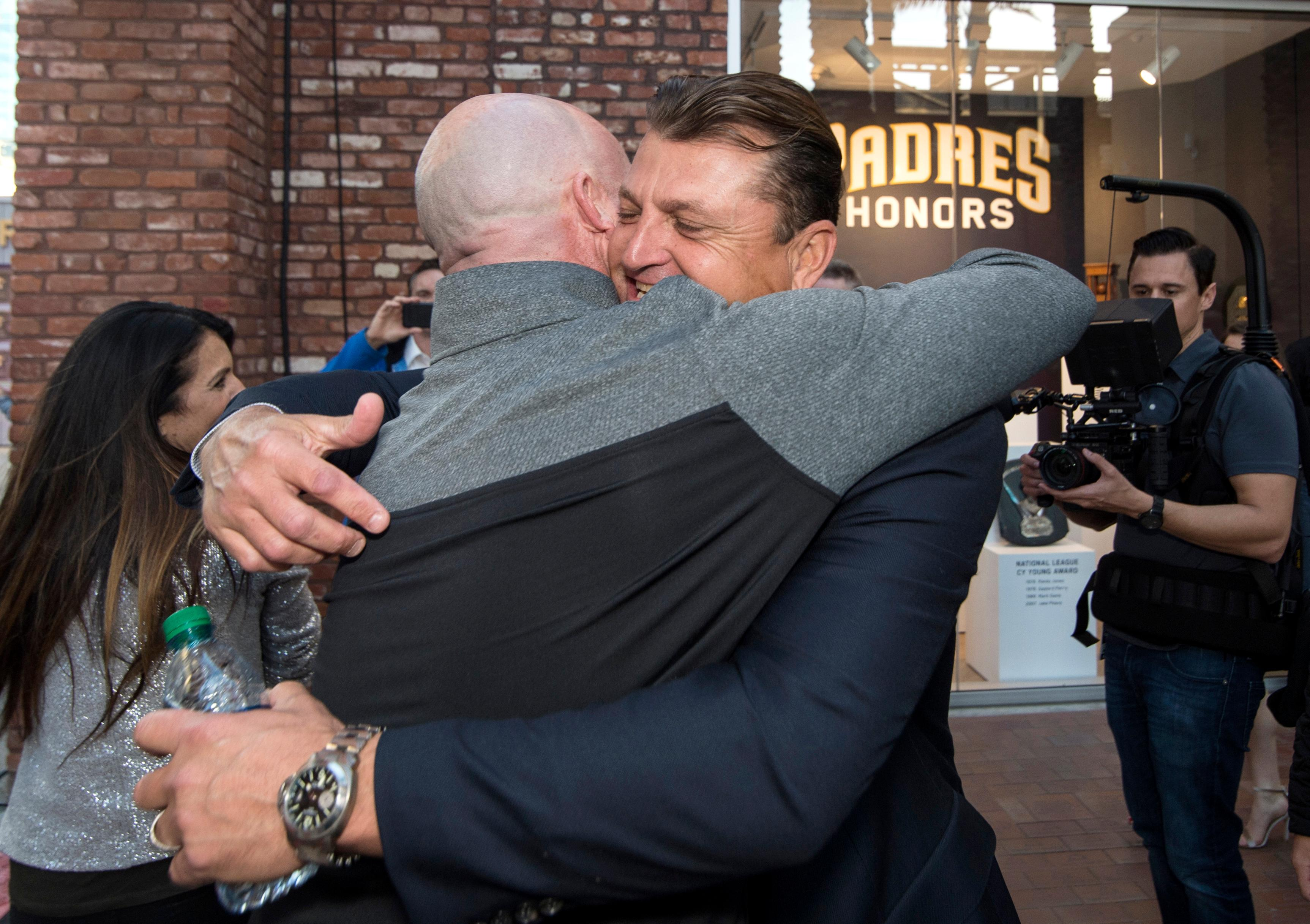 Former San Diego Padres closer Trevor Hoffman, center right, hugs former teammate Mark Sweeney before a news conference Wednesday, Jan. 24, 2018, in San Diego after Hoffman was elected to the baseball Hall of Fame. (AP Photo/Kyusung Gong)