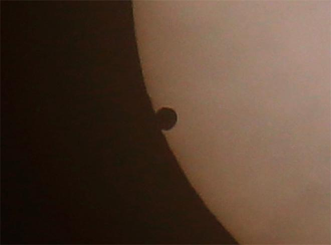 Venus begins to pass in front of the sun, as visible from Hong Kong, Wednesday, June 6, 2012. From the U.S. to South Korea, people around the world turned their attention to the daytime sky on Tuesday and early Wednesday in Asia to make sure they caught the once-in-a-lifetime sight of the transit of Venus.(AP Photo/Vincent Yu)