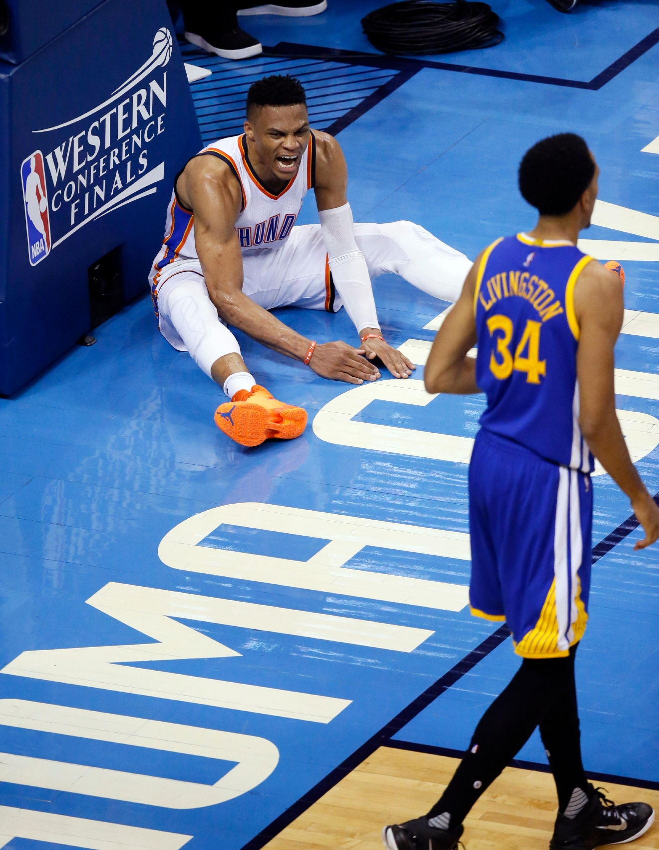 Oklahoma City Thunder guard Russell Westbrook (0) reacts as Golden State Warriors guard Shaun Livingston (34) walks by during the second half in Game 4 of the NBA basketball Western Conference finals in Oklahoma City, Tuesday, May 24, 2016. (AP Photo/Sue Ogrocki)