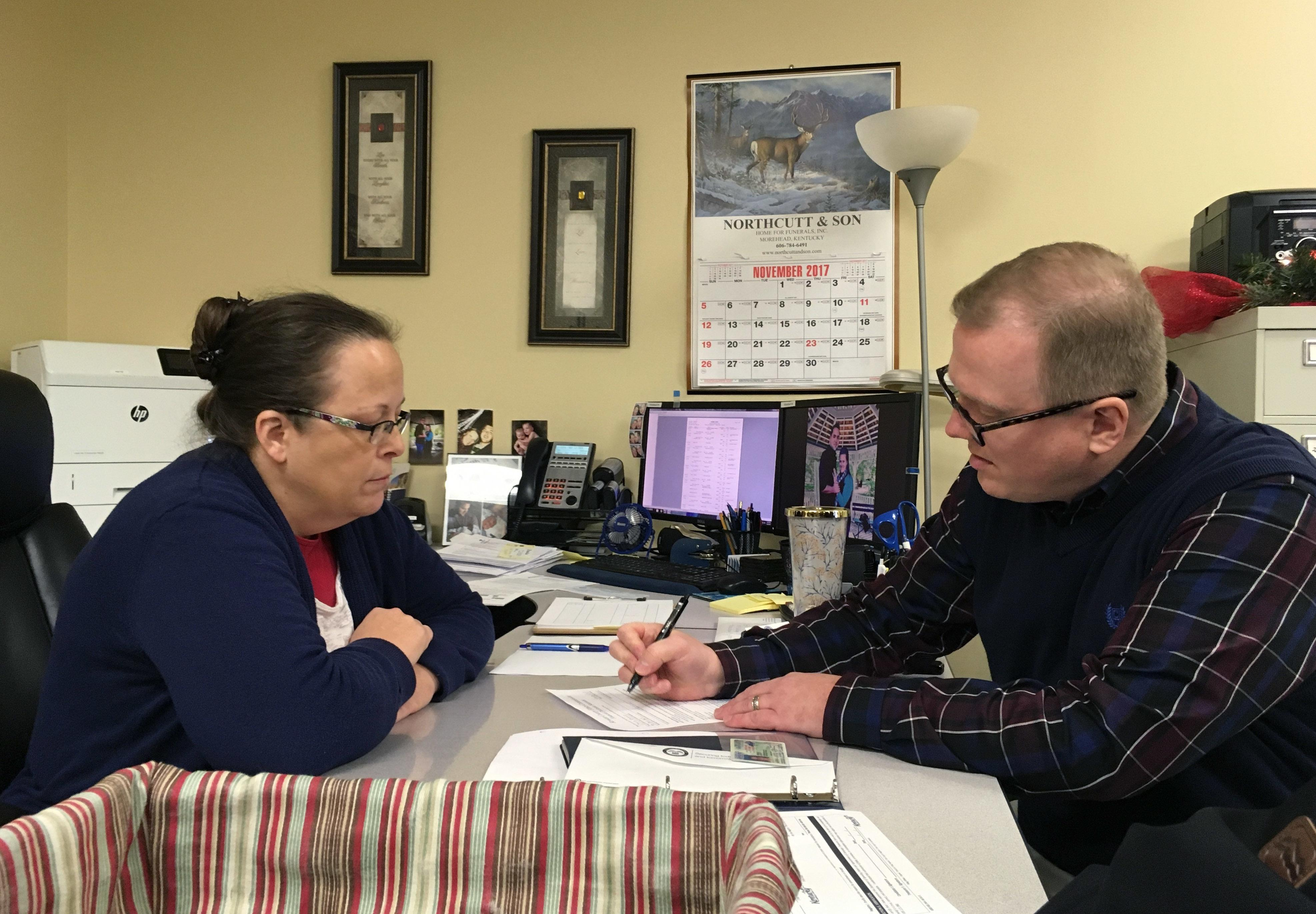 David Ermold, right, files to run for Rowan County Clerk in Kentucky as Clerk Kim Davis look on Wednesday, Dec. 6, 2017,  in Morehead, Ky. Davis denied Ermold and his husband a marriage license two years ago because she was opposed to gay marriage for religious reasons. (AP Photo/Adam Beam)