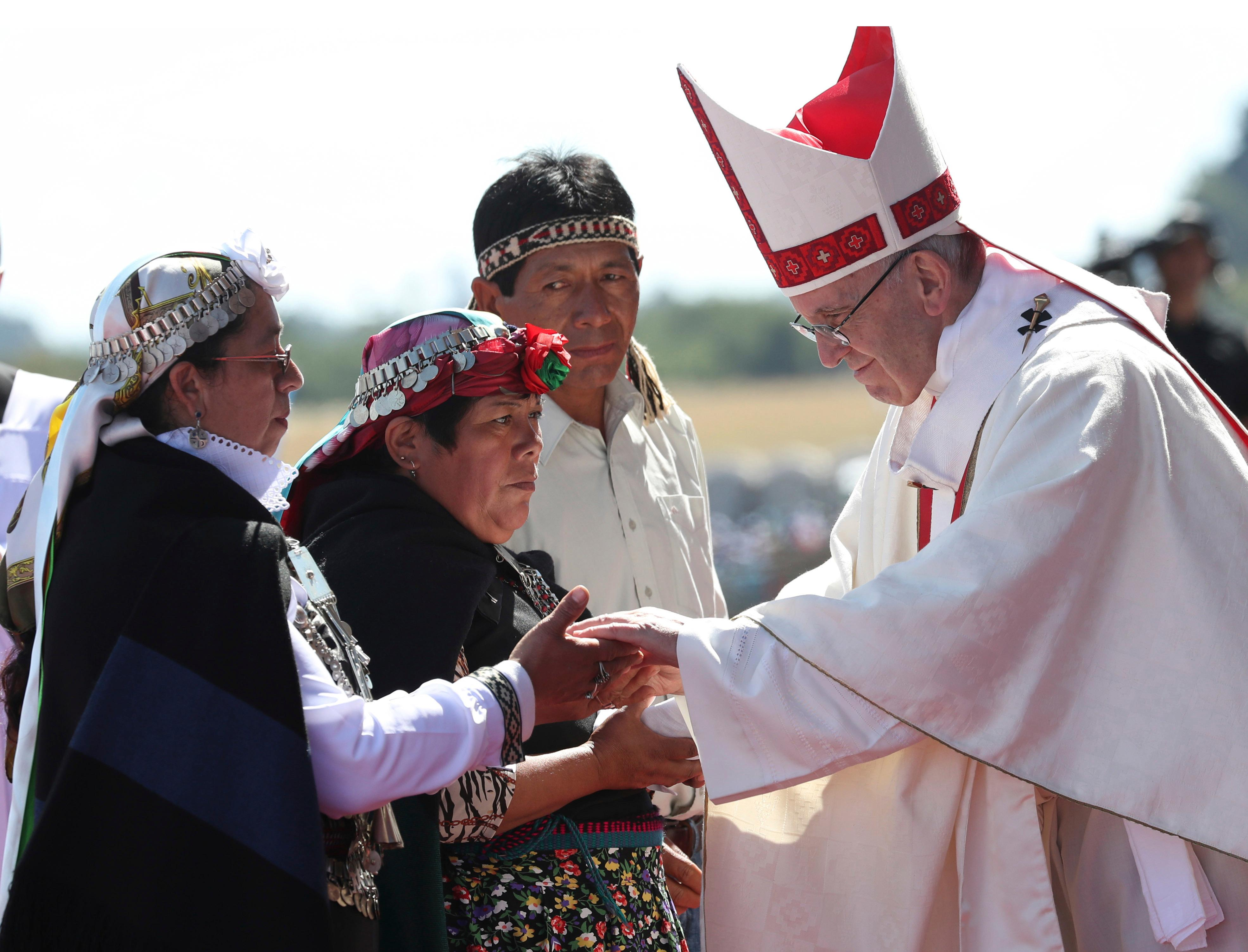 Pope Francis greets Mapuches in an offertory of a Mass at the Maquehue Air Base, in Temuco, Chile, Wednesday, Jan. 17, 2018. Francis is urging the Mapuche people to reject violence in pushing their cause. Francis made the comments Wednesday while celebrating Mass in Temuco. The city is the capital of the Araucania region, where many of Chile's estimated 1 million people of Mapuche descent live. (AP Photo/Alessandra Tarantino)