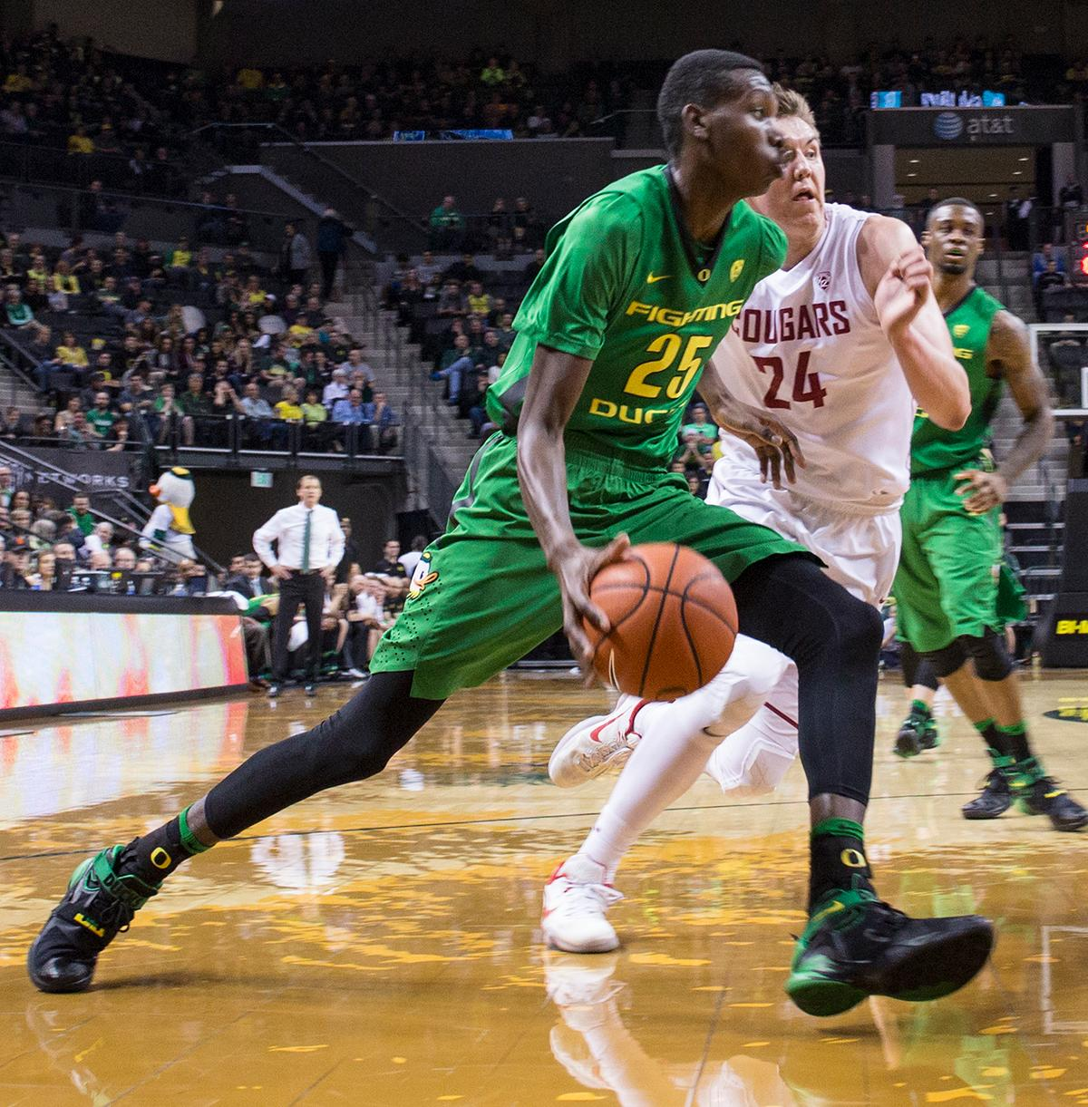 Oregon Ducks' Chris Boucher (#25) drives toward the basket against Washington State Cougars' Josh Hawkinson (#24). The Ducks beat the Cougars 76-62. Kianna Cabuco, Oregon News Lab